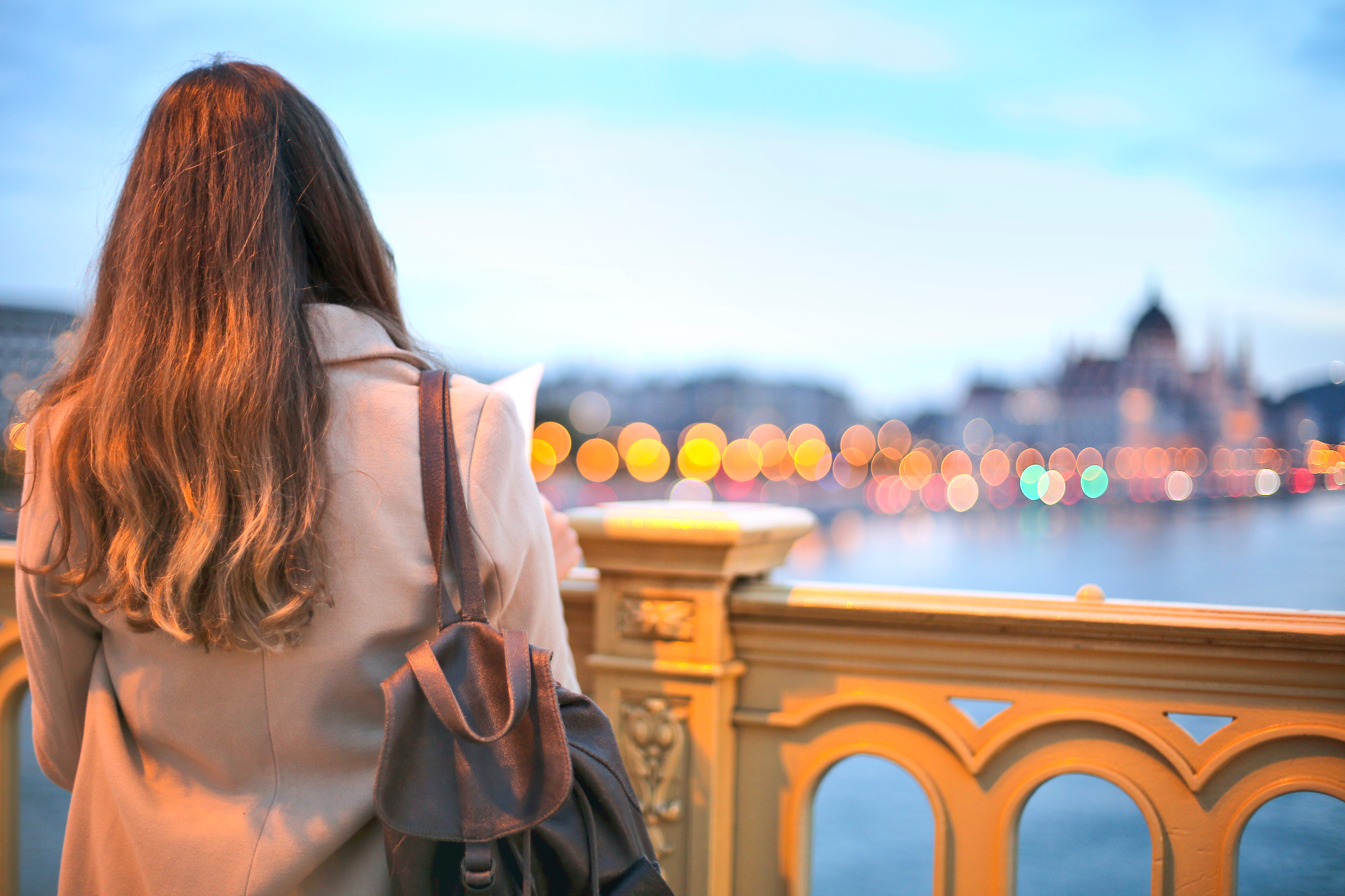 Woman wearing trench coat and black leather backpack photo