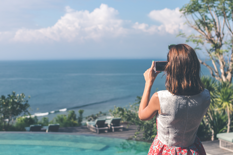 Woman wearing white and red sleeveless dress taking photo of beach