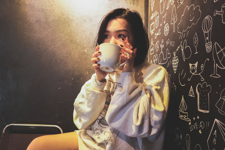 Woman wearing white over shirt holding white ceramic mug beside black printed wall photo