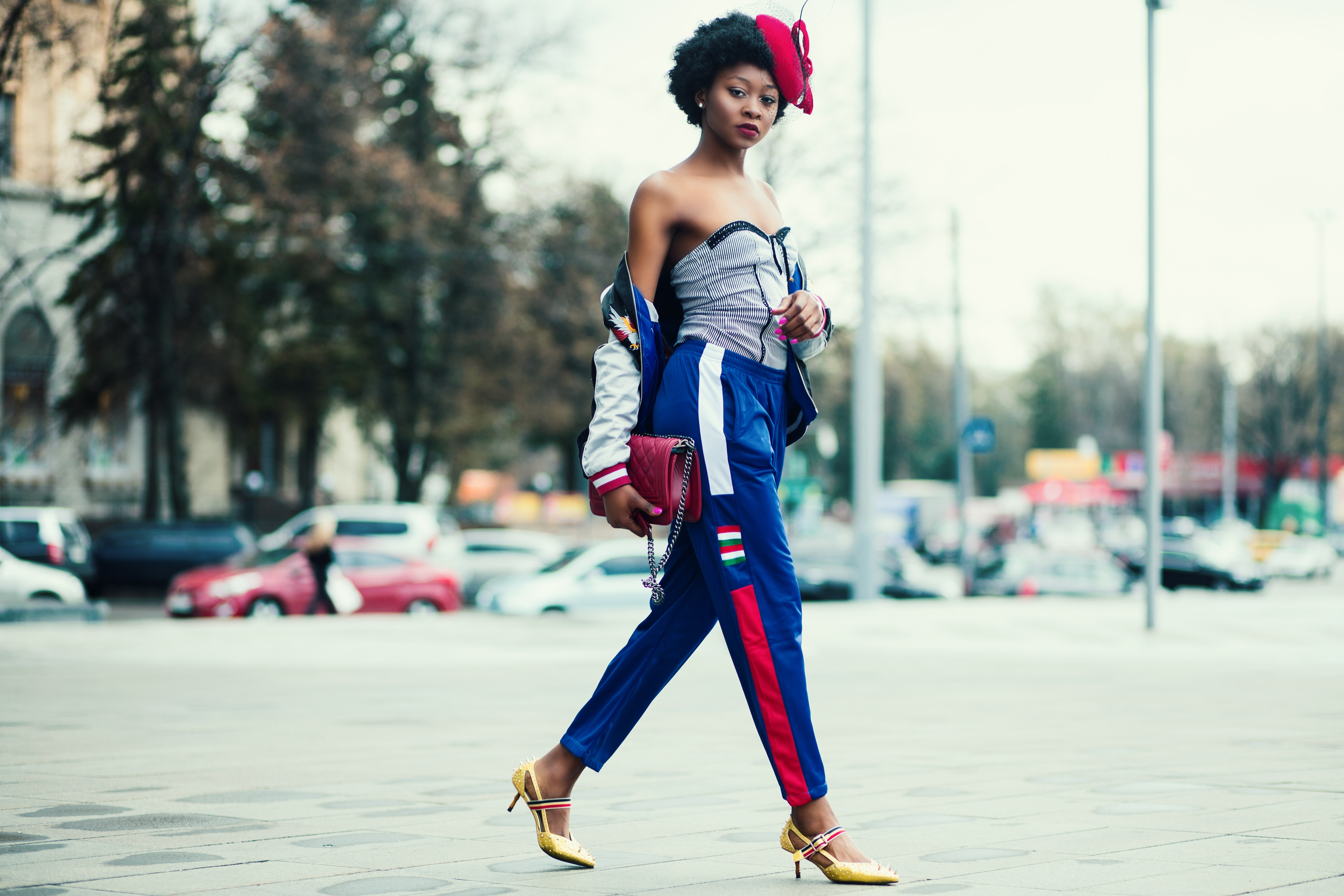 Woman wearing white sweetheart neckline shirt with blue and red pants walking across the street photo