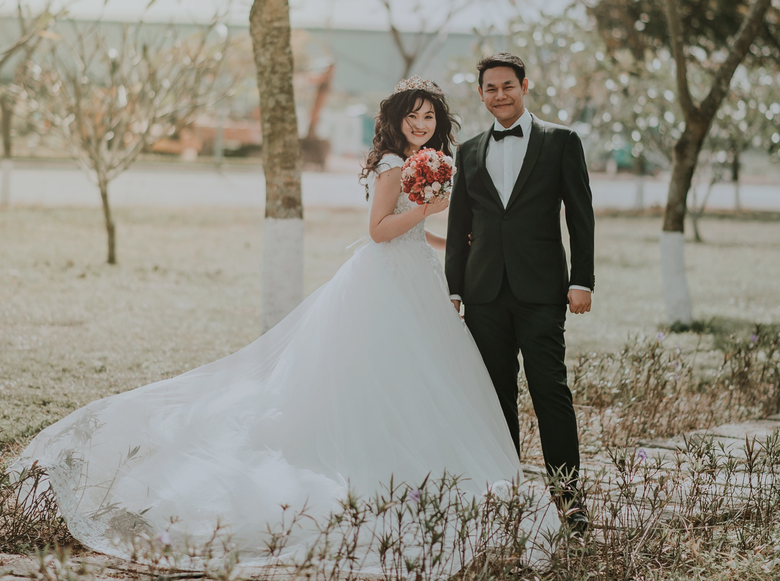 Woman wearing white wedding ball beside man wearing black notch-lapel suit on pathway near the green grass field photo