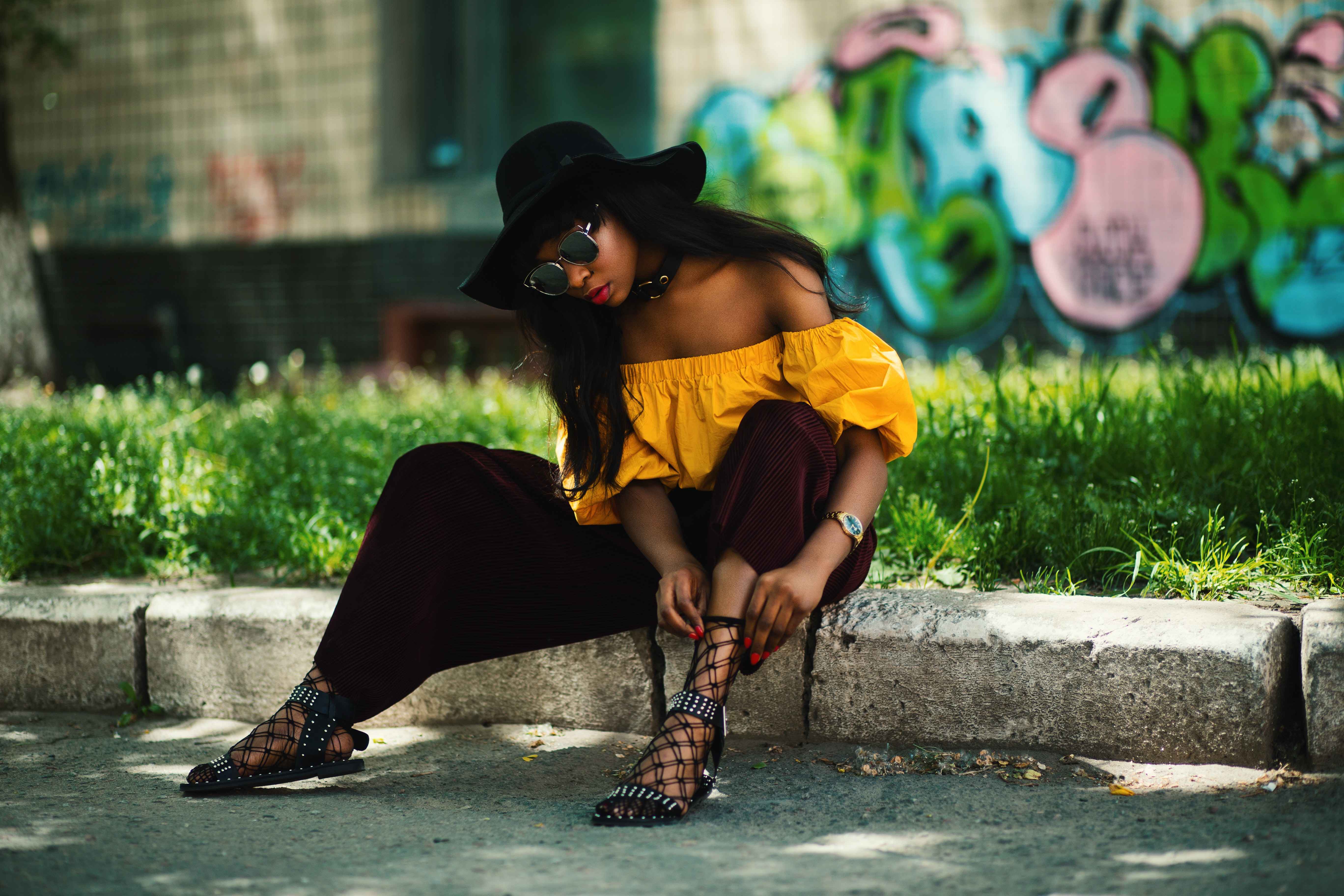 Woman wearing yellow off-shoulder top and black pants sitting on sidewalk fixing lace sandals photo
