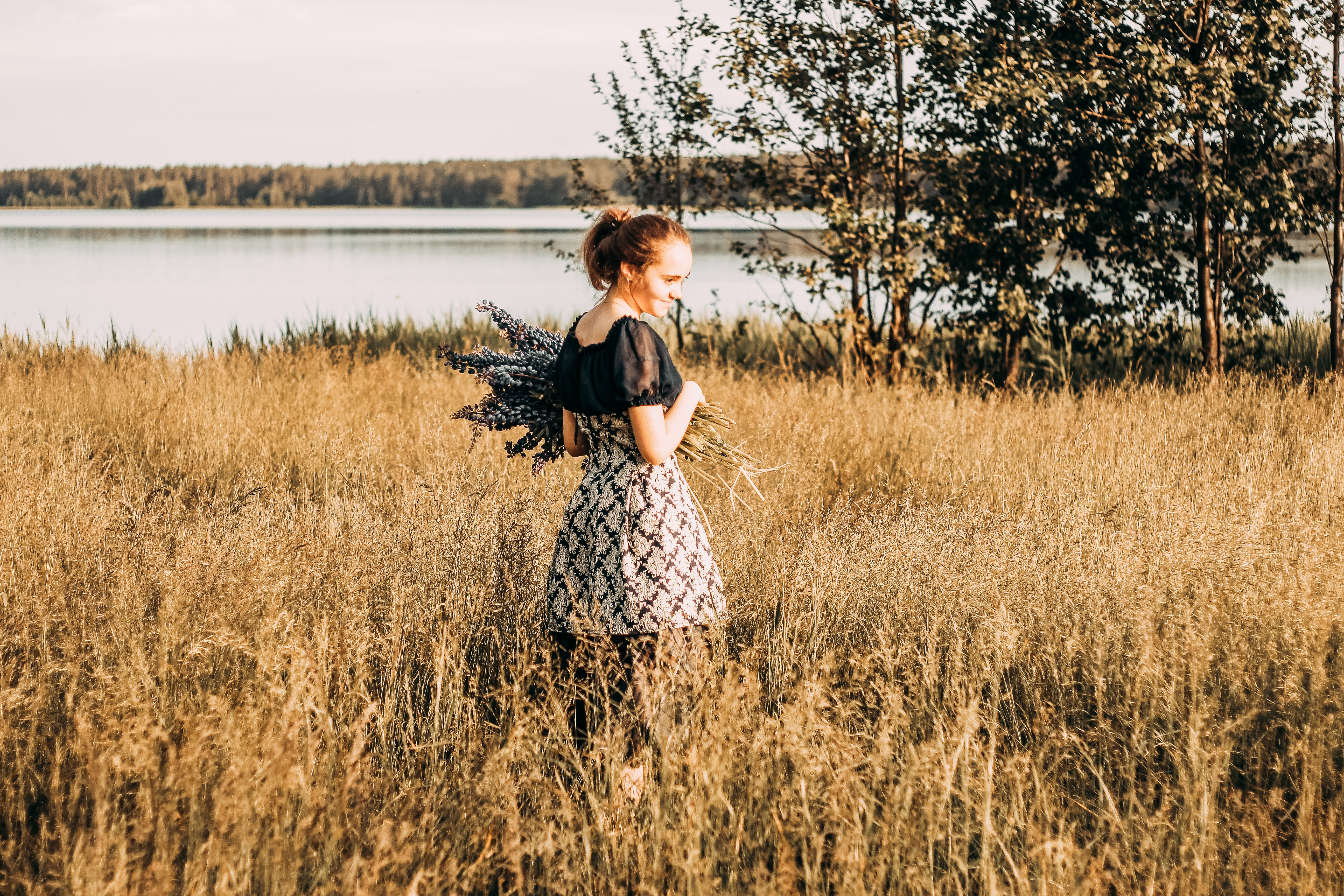 Woman wears black and grey dress stands in field photo