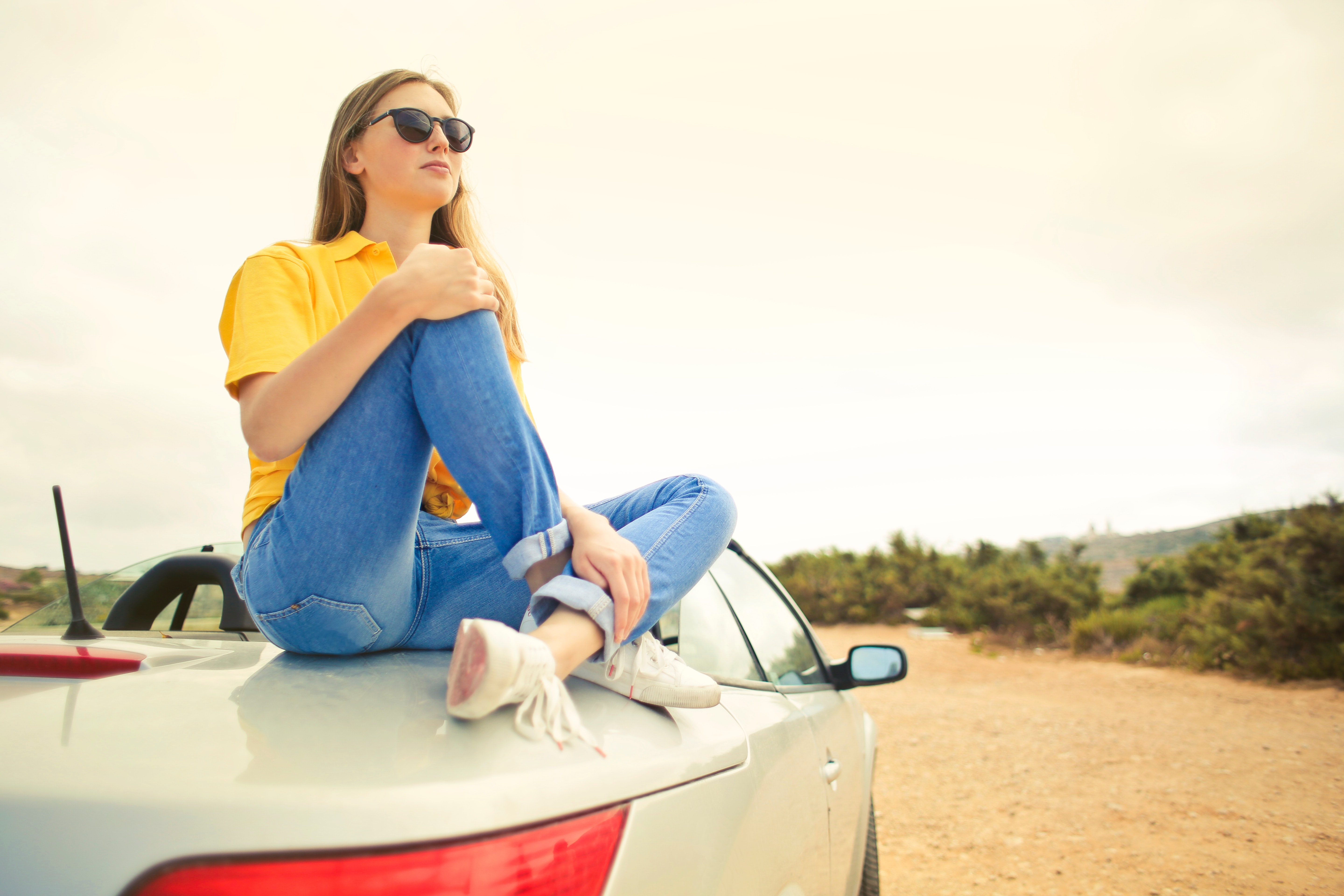 Woman wears yellow shirt and blue denim jeans sits on silver car photo