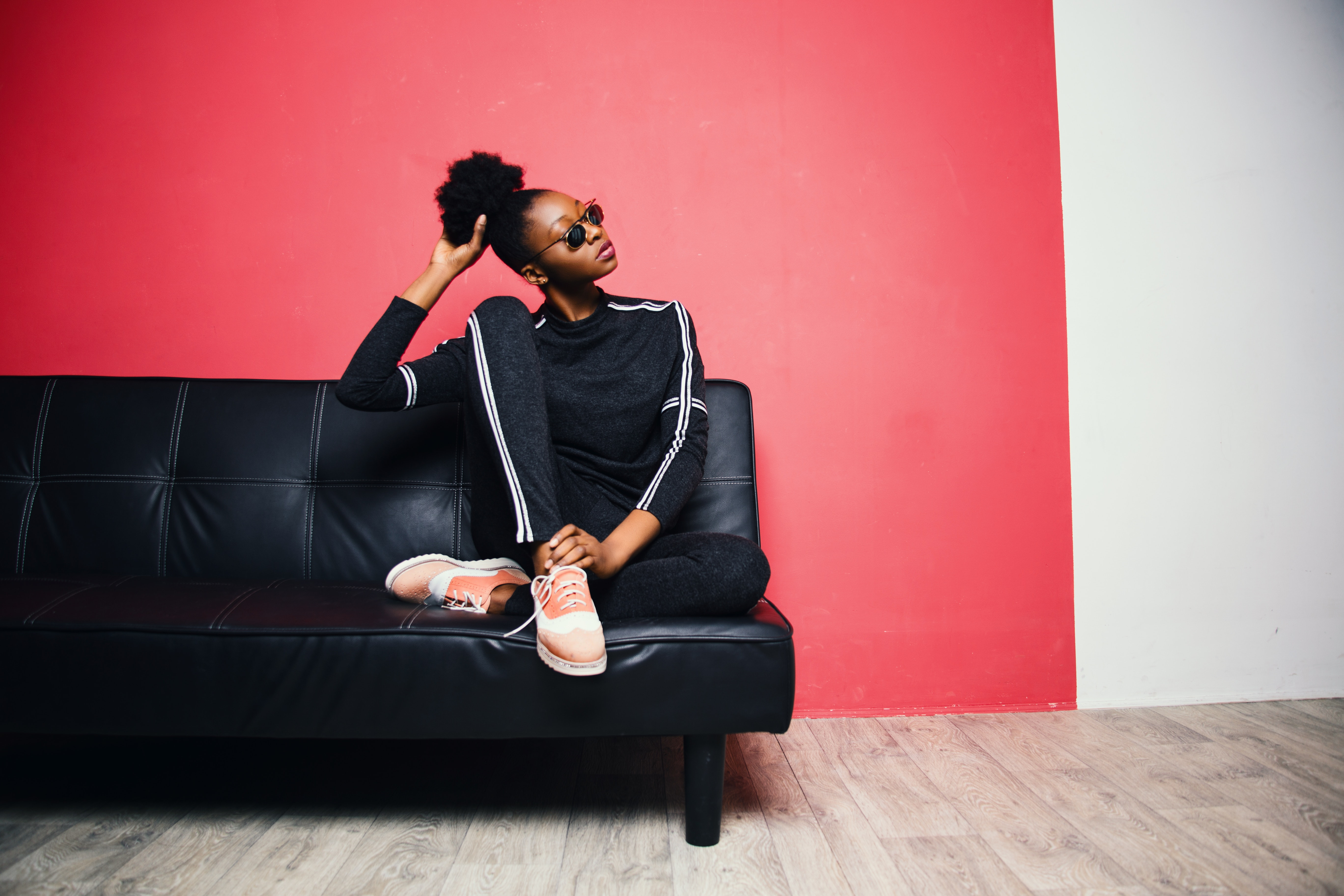 Woman with black-and-white sweater with pants sitting on black leather sofa beside red painted wall photo