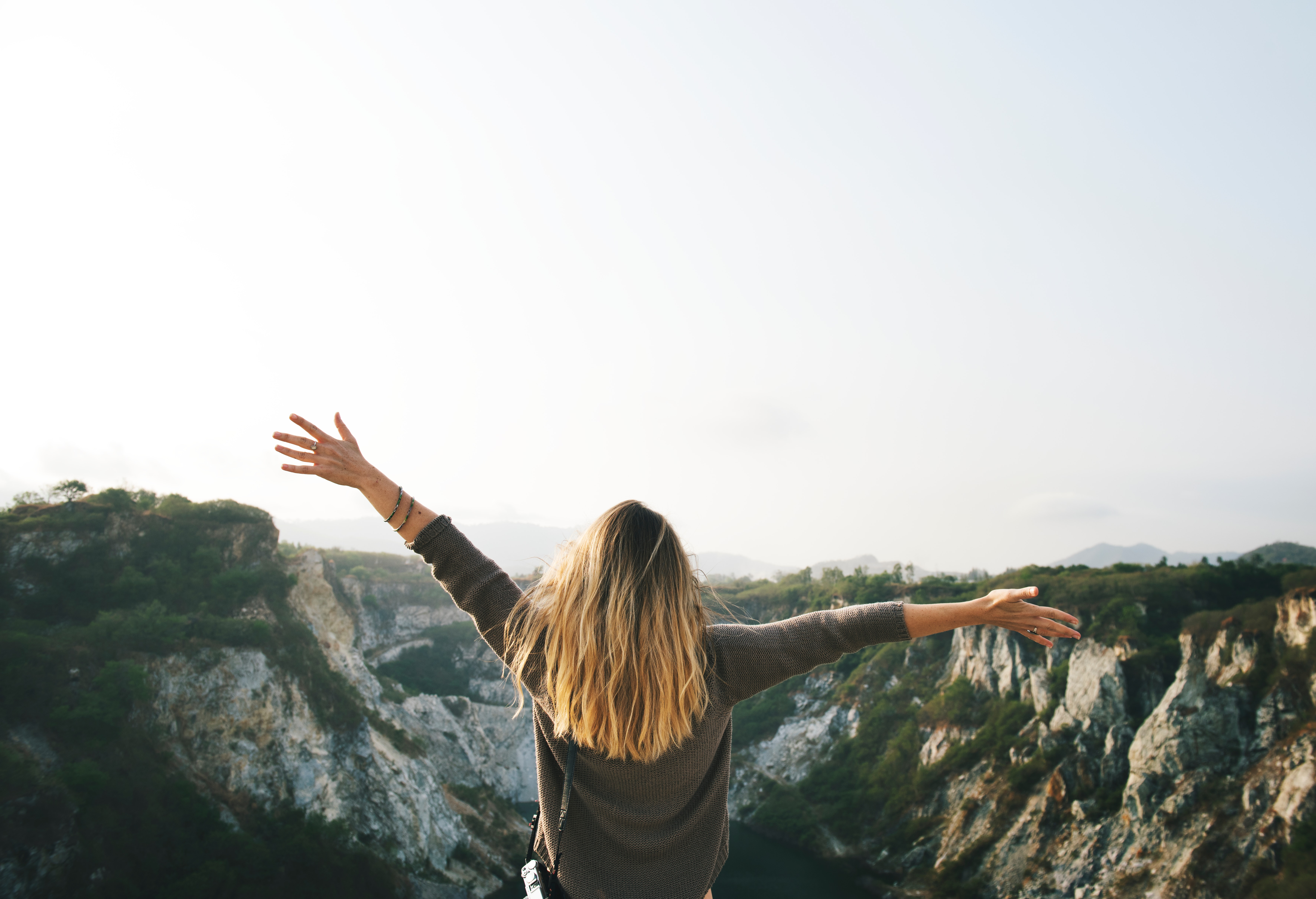 Woman with blonde hair at the top of the mountain raising her hands photo