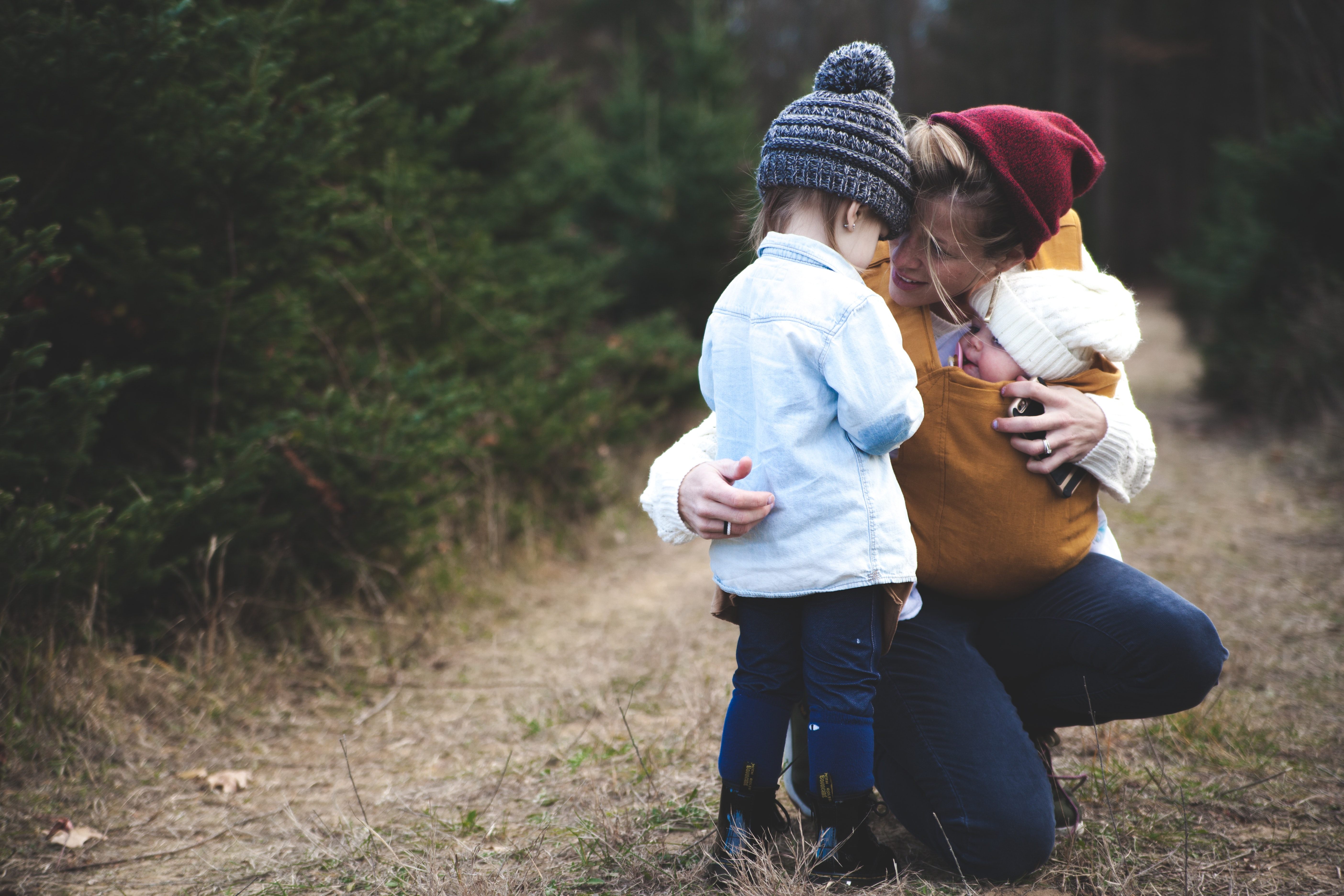 Woman with brown baby carrier and little kid in white jacket photo