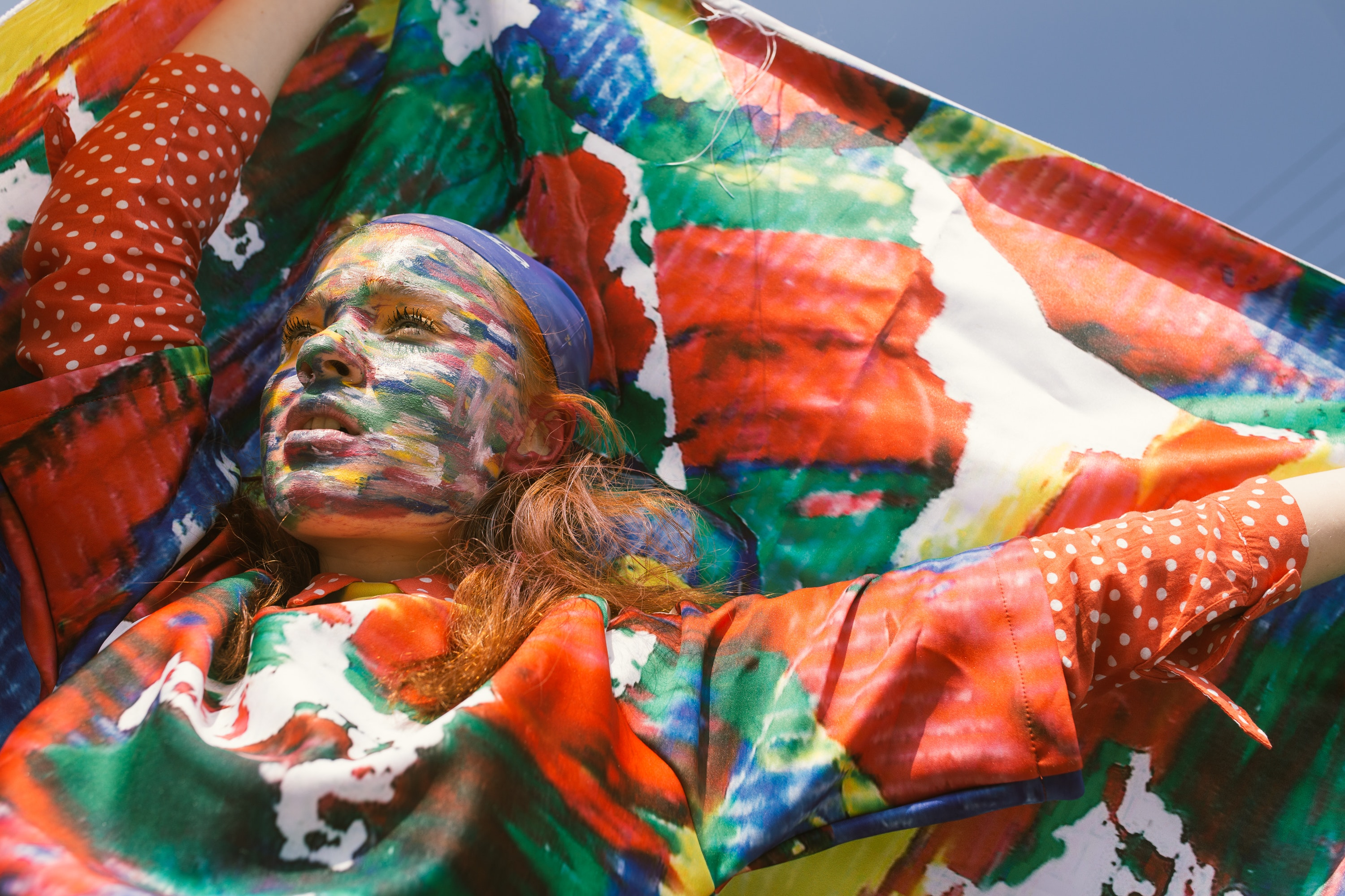 Woman with face paint raising her hands holding textile photo
