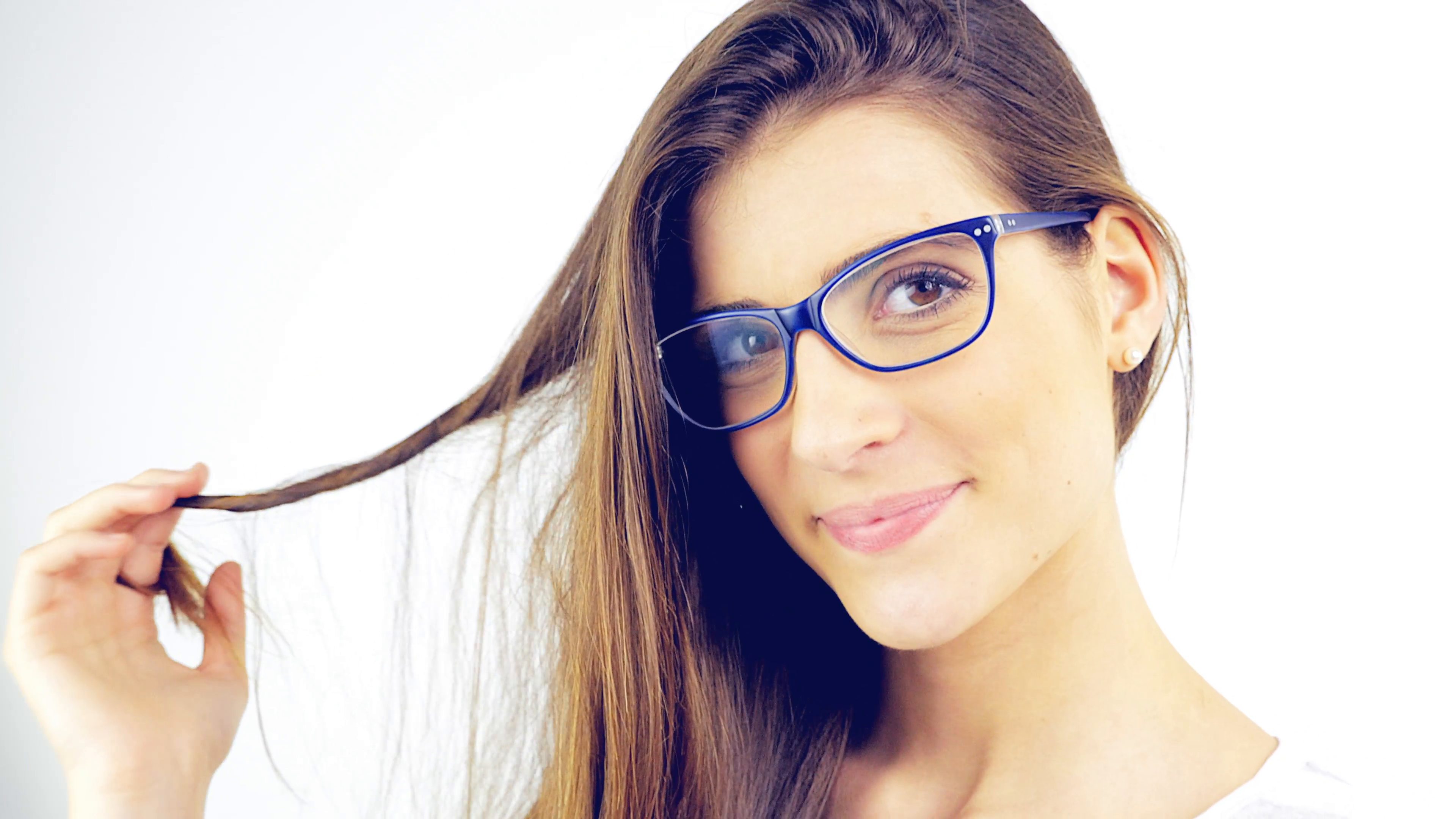 Cute young woman with glasses playing with hair blinking to camera ...
