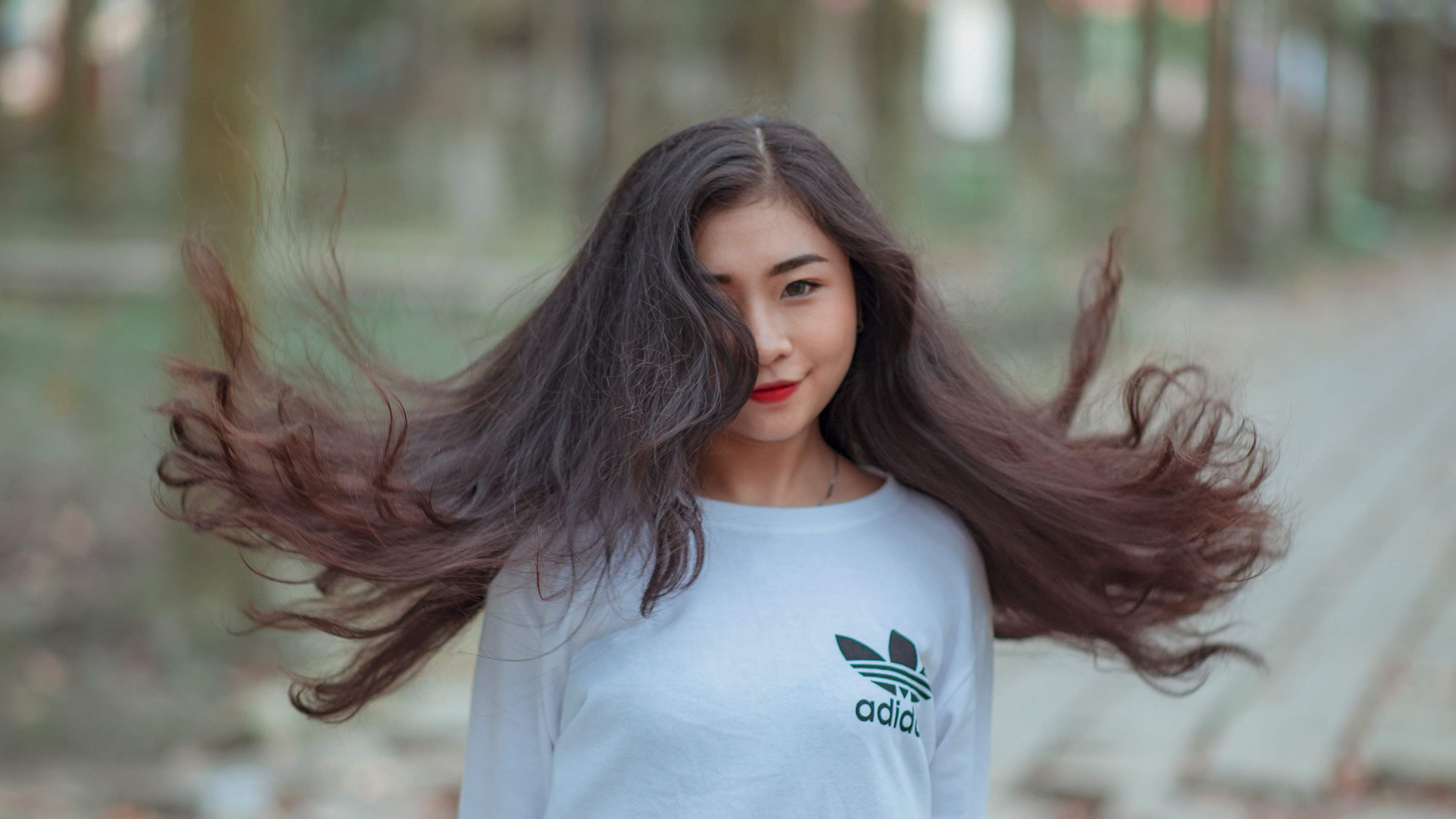 Woman with long hair waving on air and wearing white adidas shirt photo