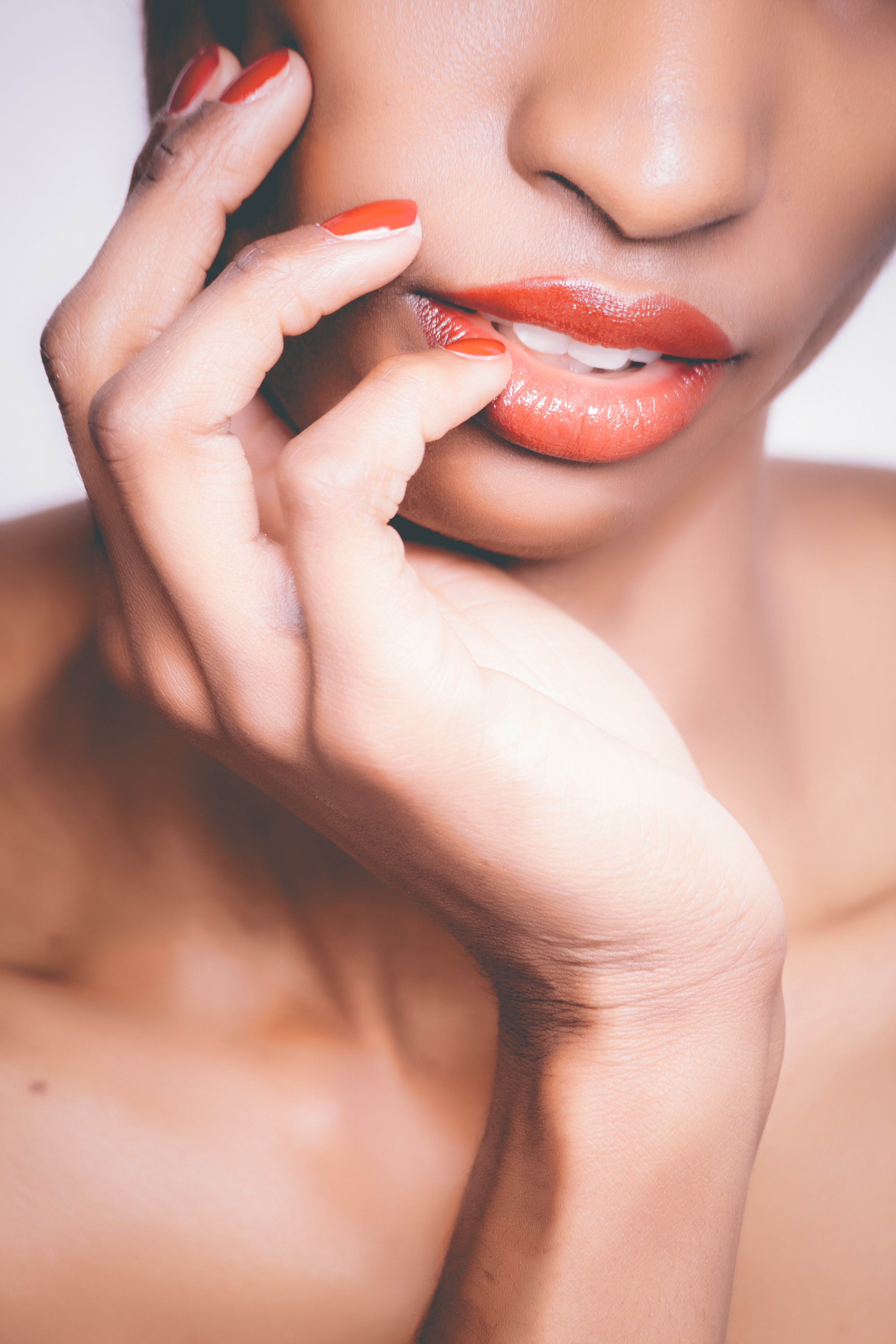 Woman with orange lipstick and manicure taking selfie photo