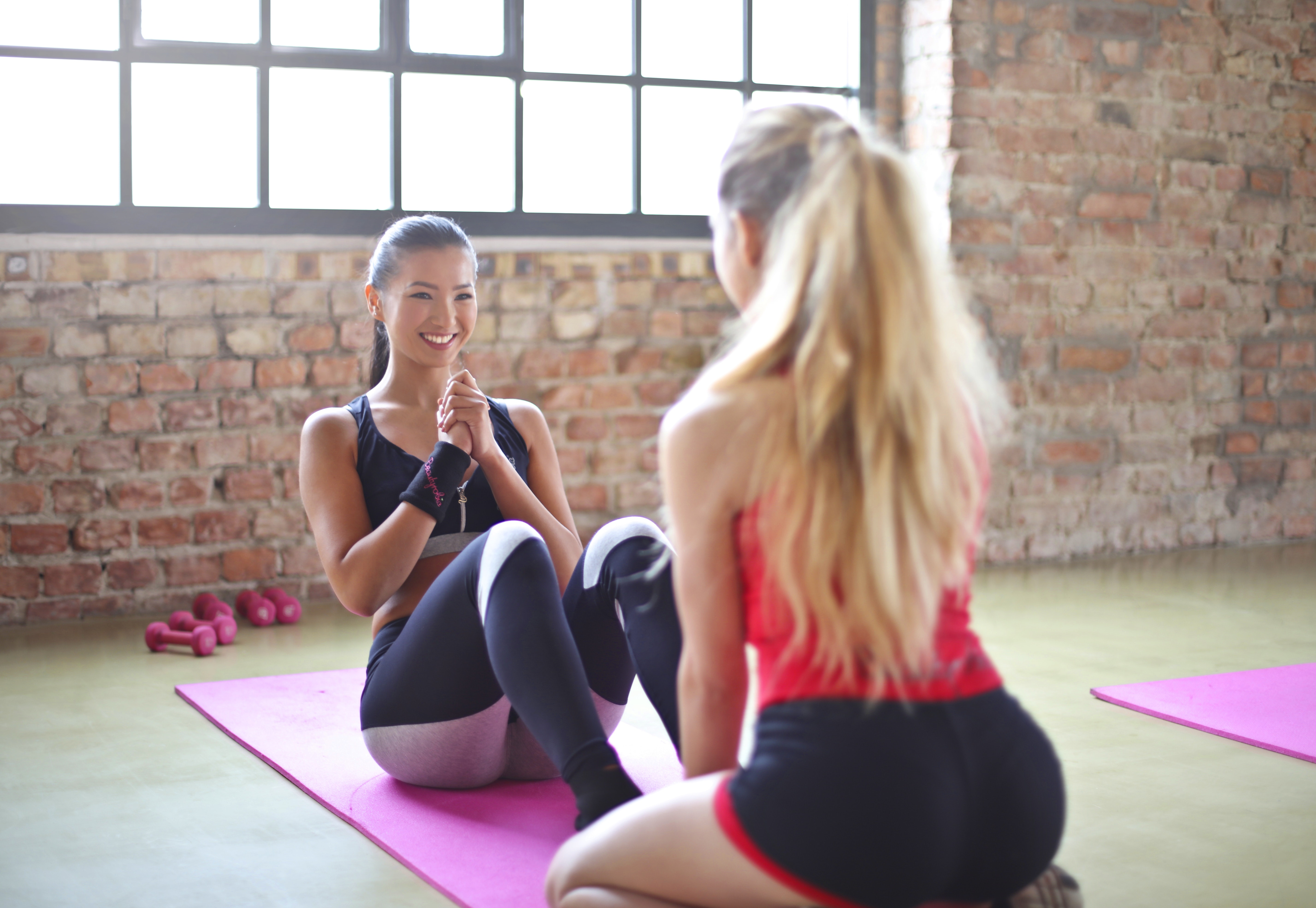Woman with red top and black shorts on purple yoga mat photo