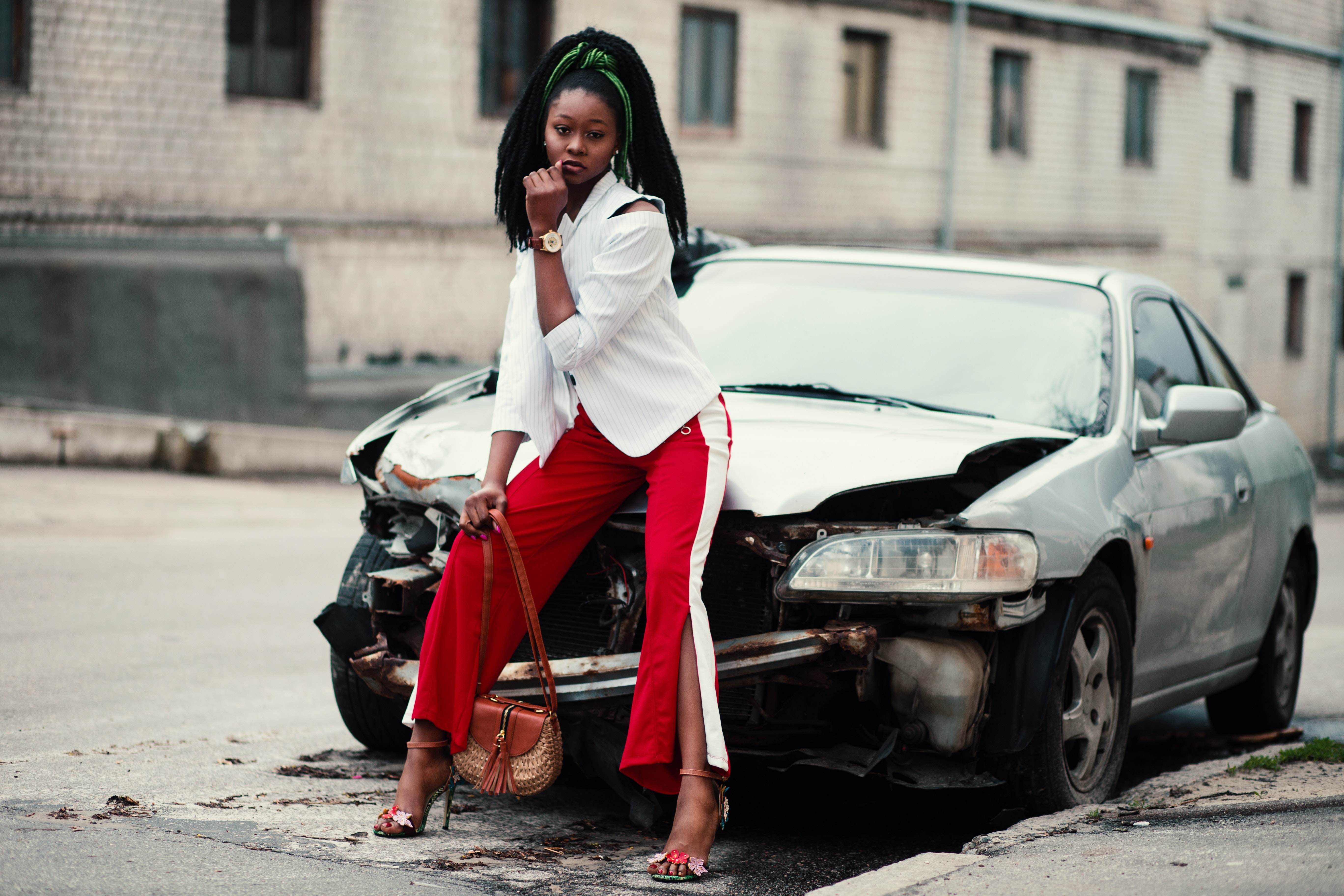 Woman with white long-sleeved shirt, red ,and white slit pants and pair of black open-toe d'orsay heel sandals sitting on wrecked silver car photo