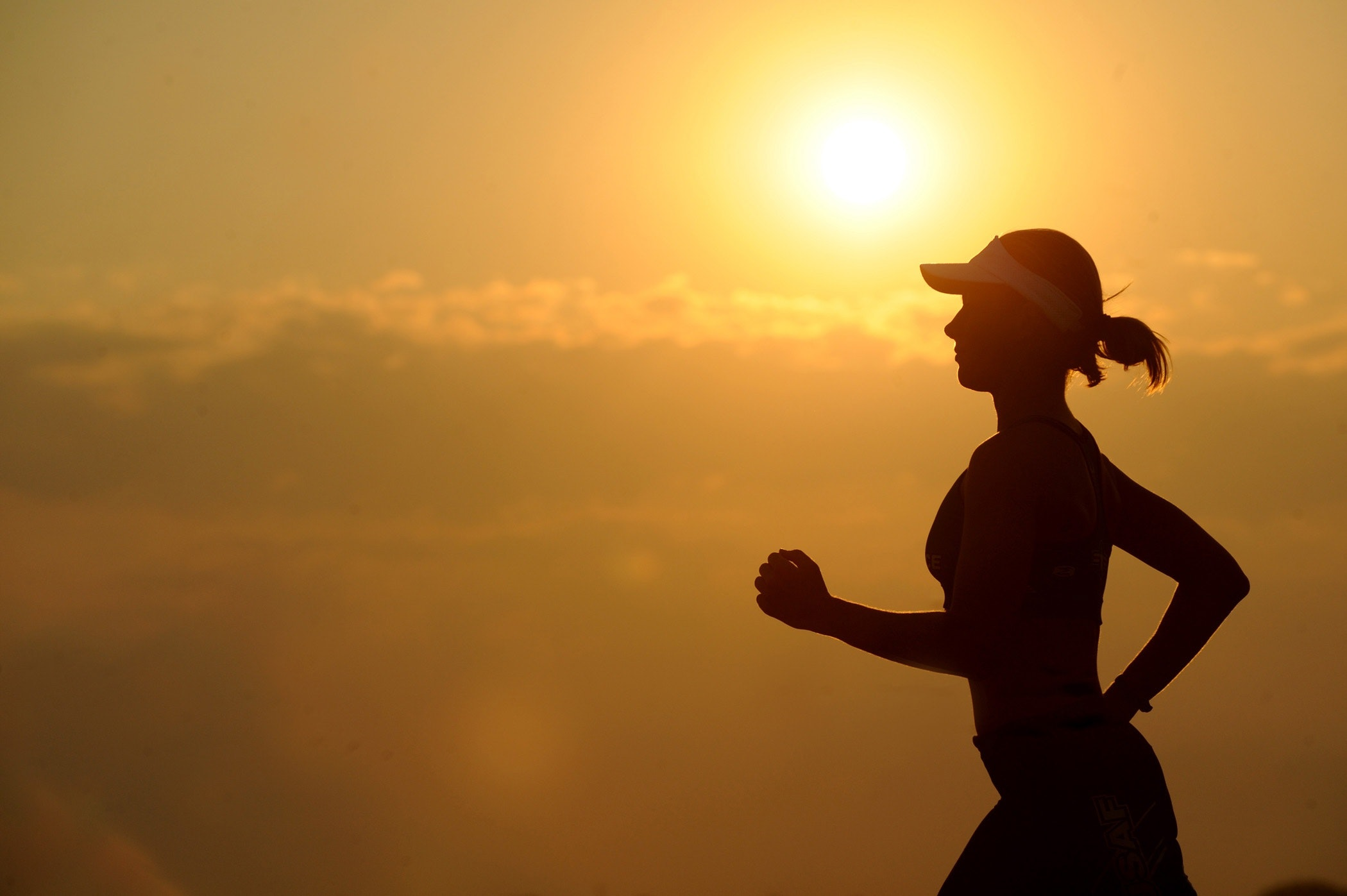 Woman with white sunvisor running photo