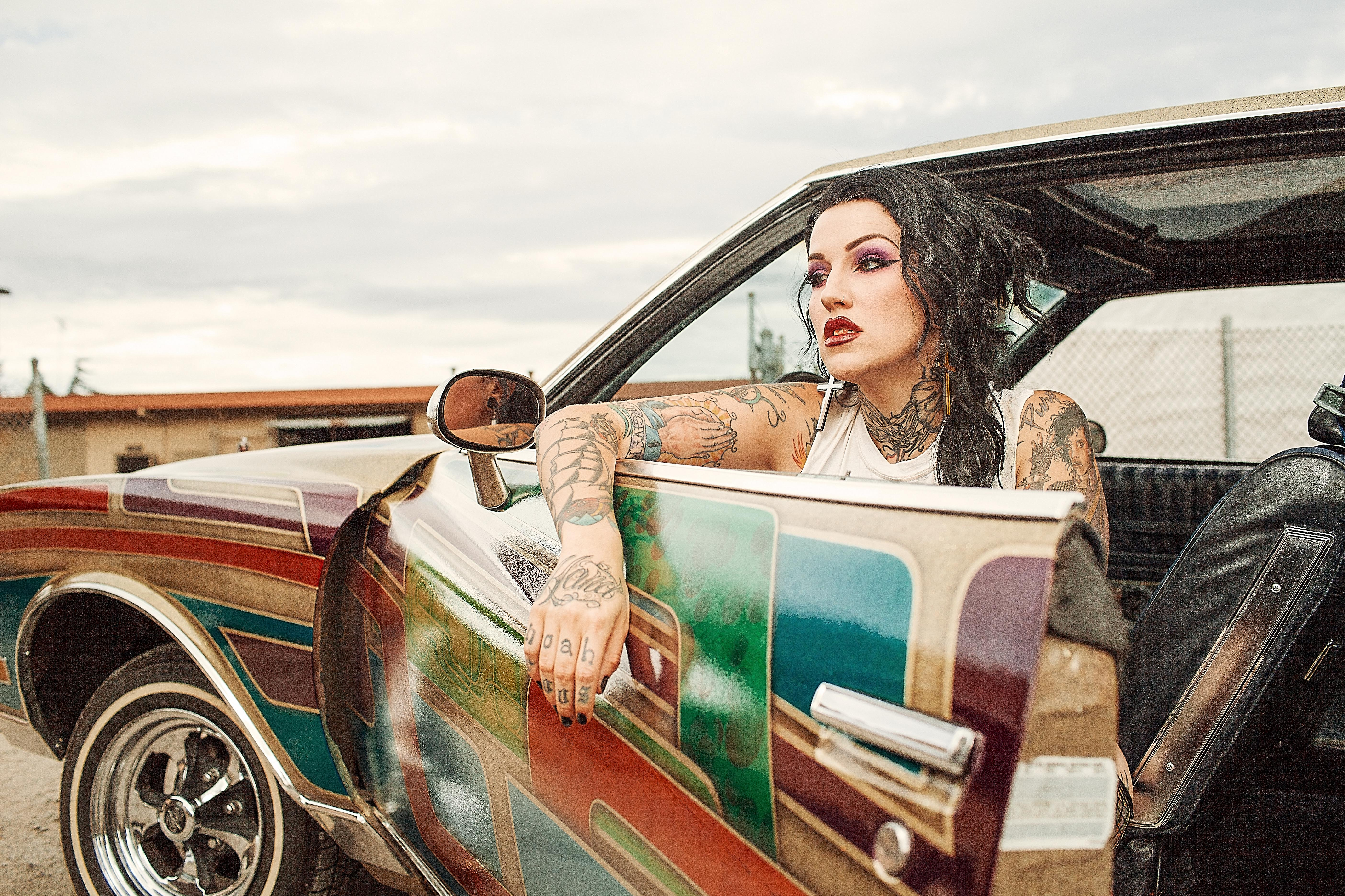 Woman with white tank top inside classic multicolored car photo
