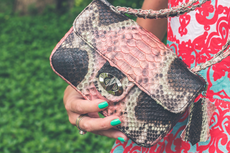 Women holding pink and black snakeskin sling bag photo
