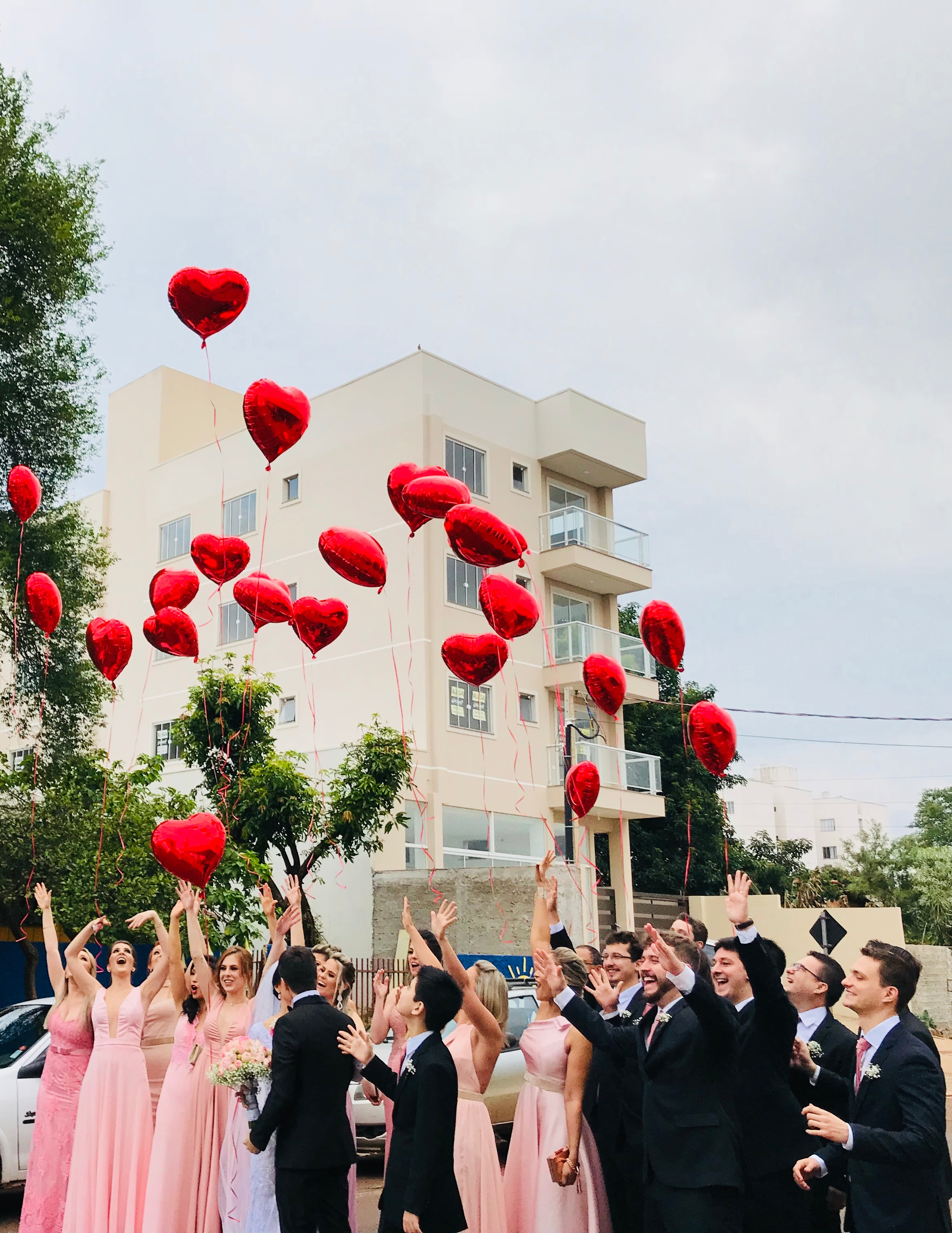 Women wearing pink dresses and men wearing black suit jacket and pants raising hands with red heart balloons photo