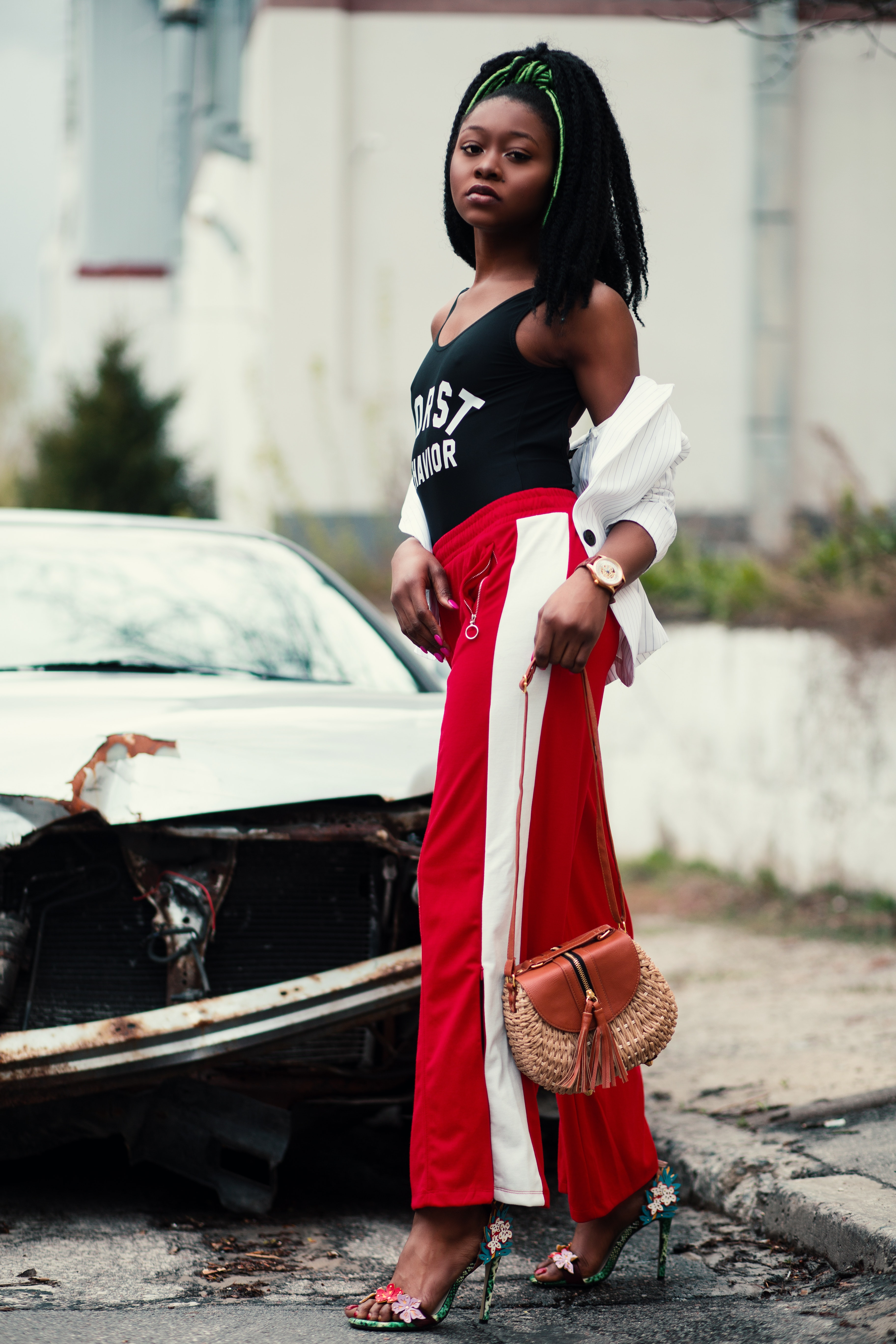 Women's black tank top and red track pants walking on street photo