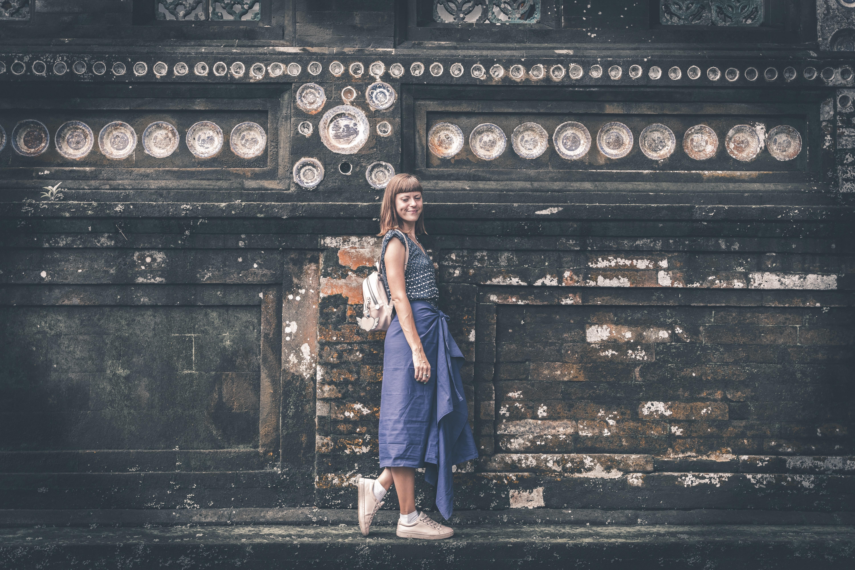 Women's blue sleeveless shirt near gray concrete wall photo