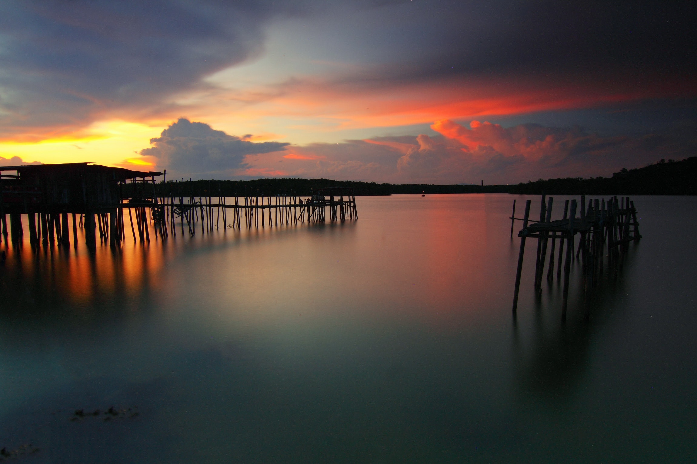 Wooden boardwalk on body of water during dawn photo