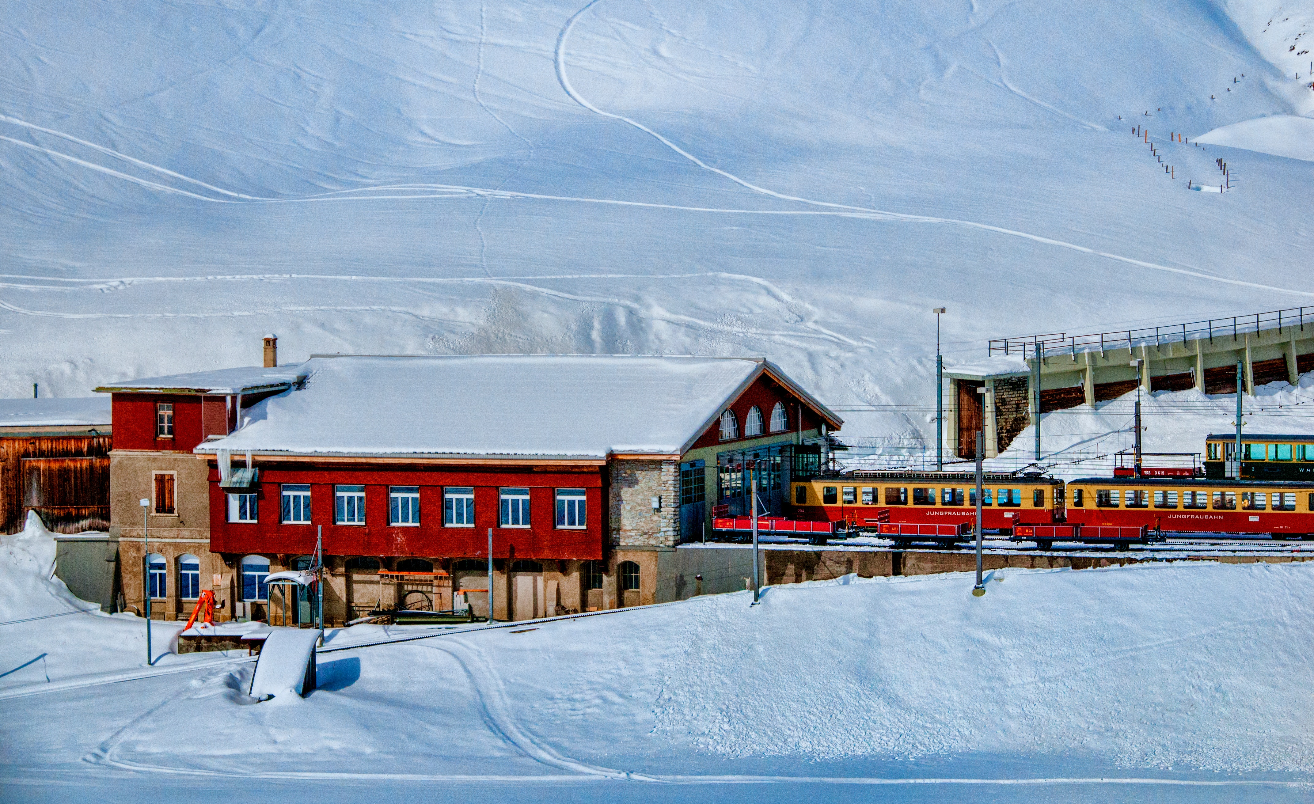 Yellow and red train beside snowy mountain photo