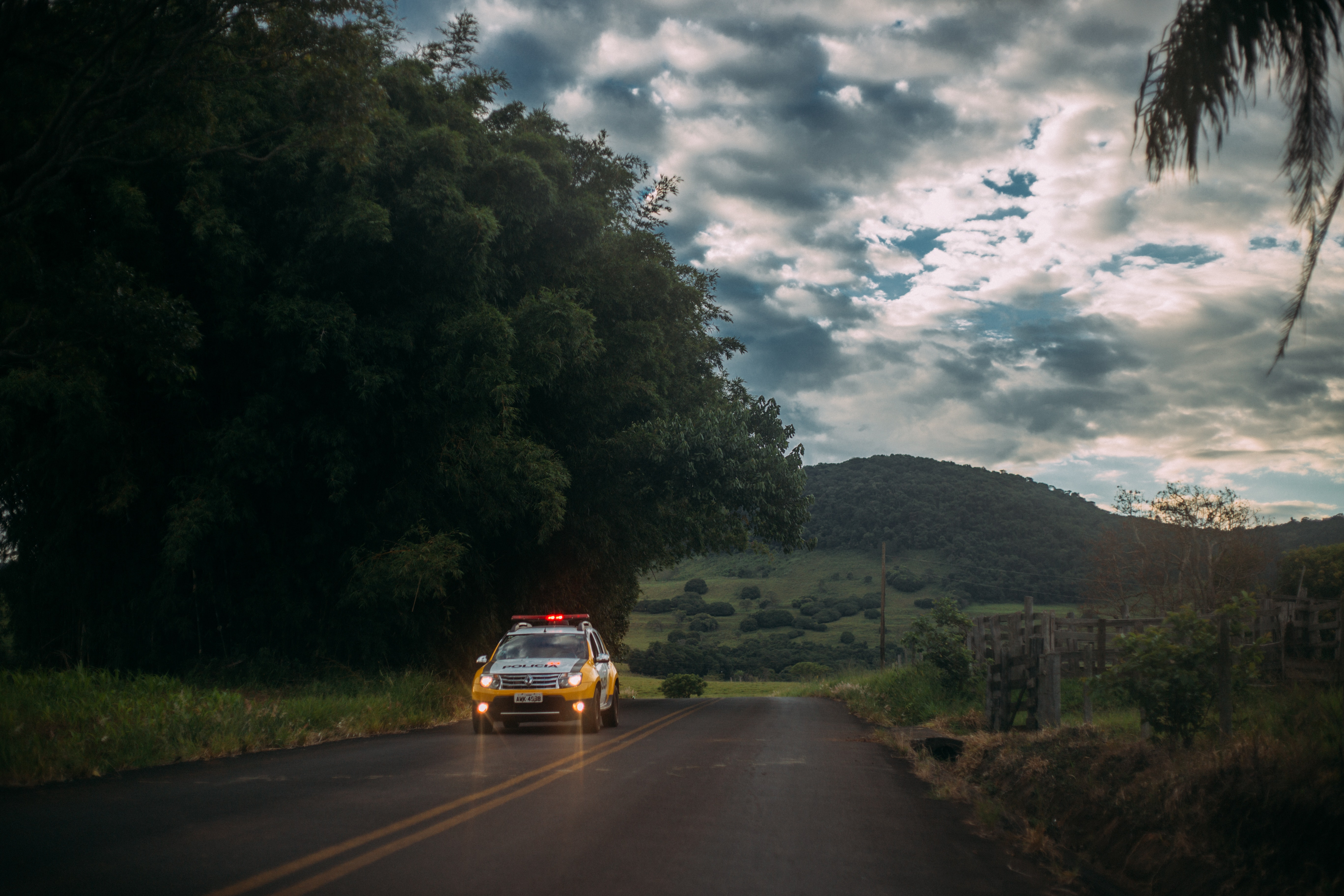 Yellow and white police car lone on the road photo
