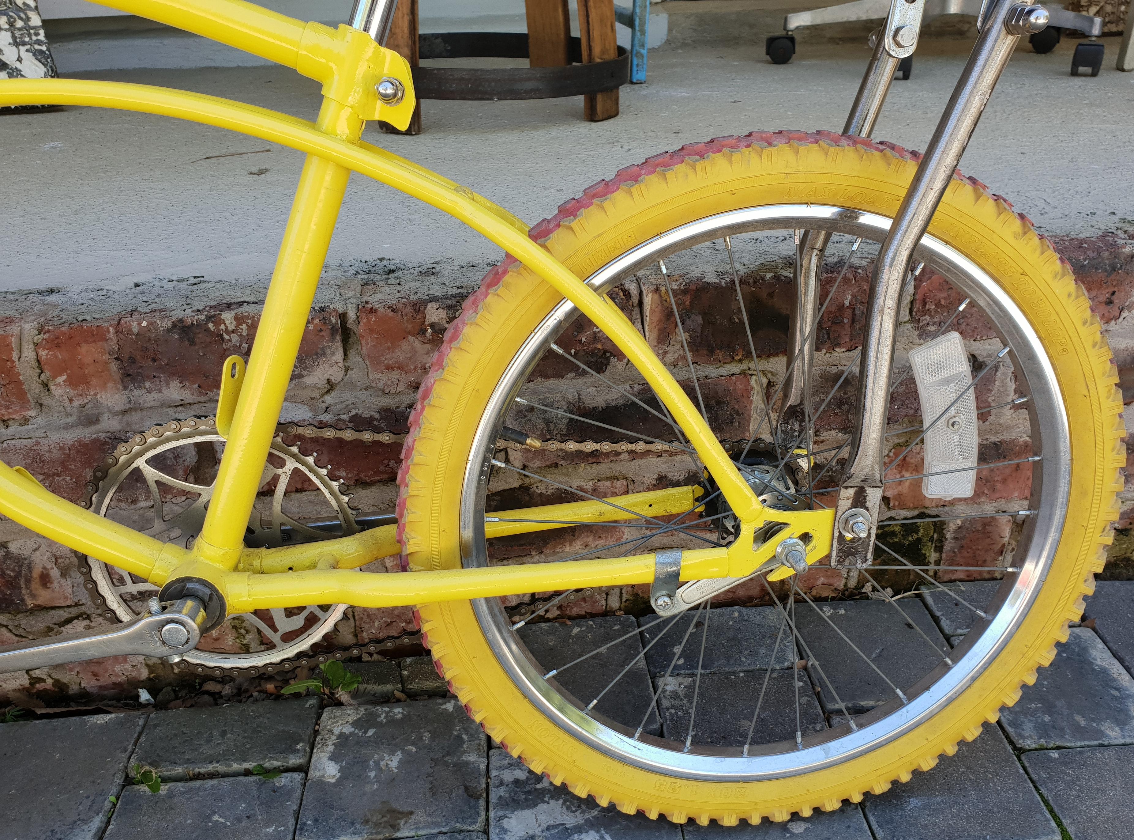 Yellow bike over the wall photo