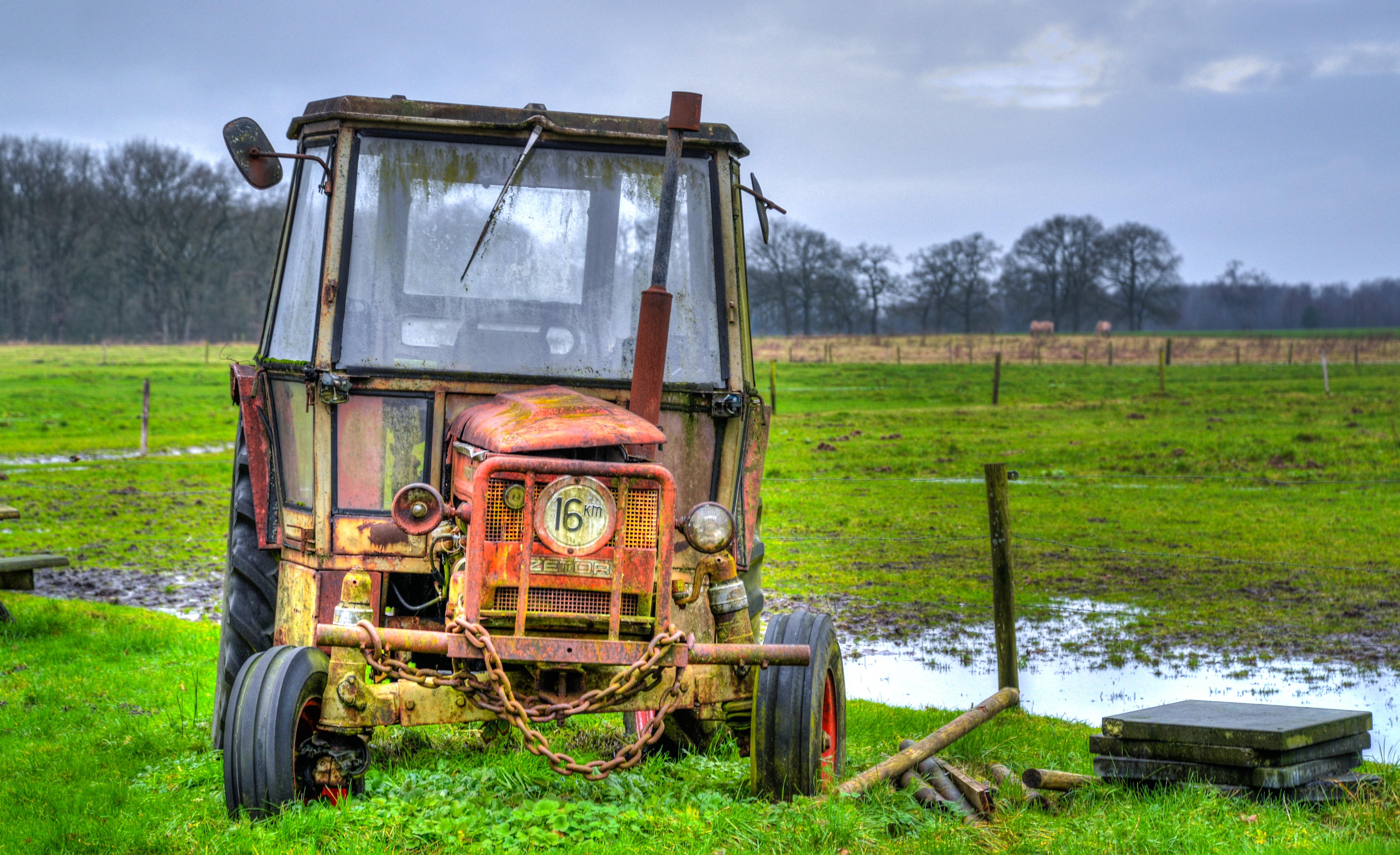 Yellow farm equipment on green grass field photo