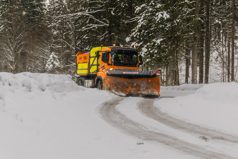 Yellow, orange, and black truck plowing snow photo