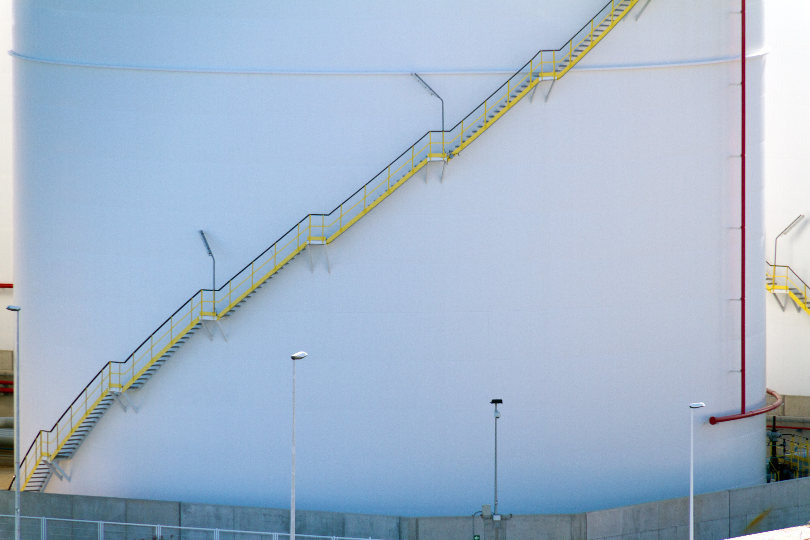 Yellow stairs on a white storage tank photo