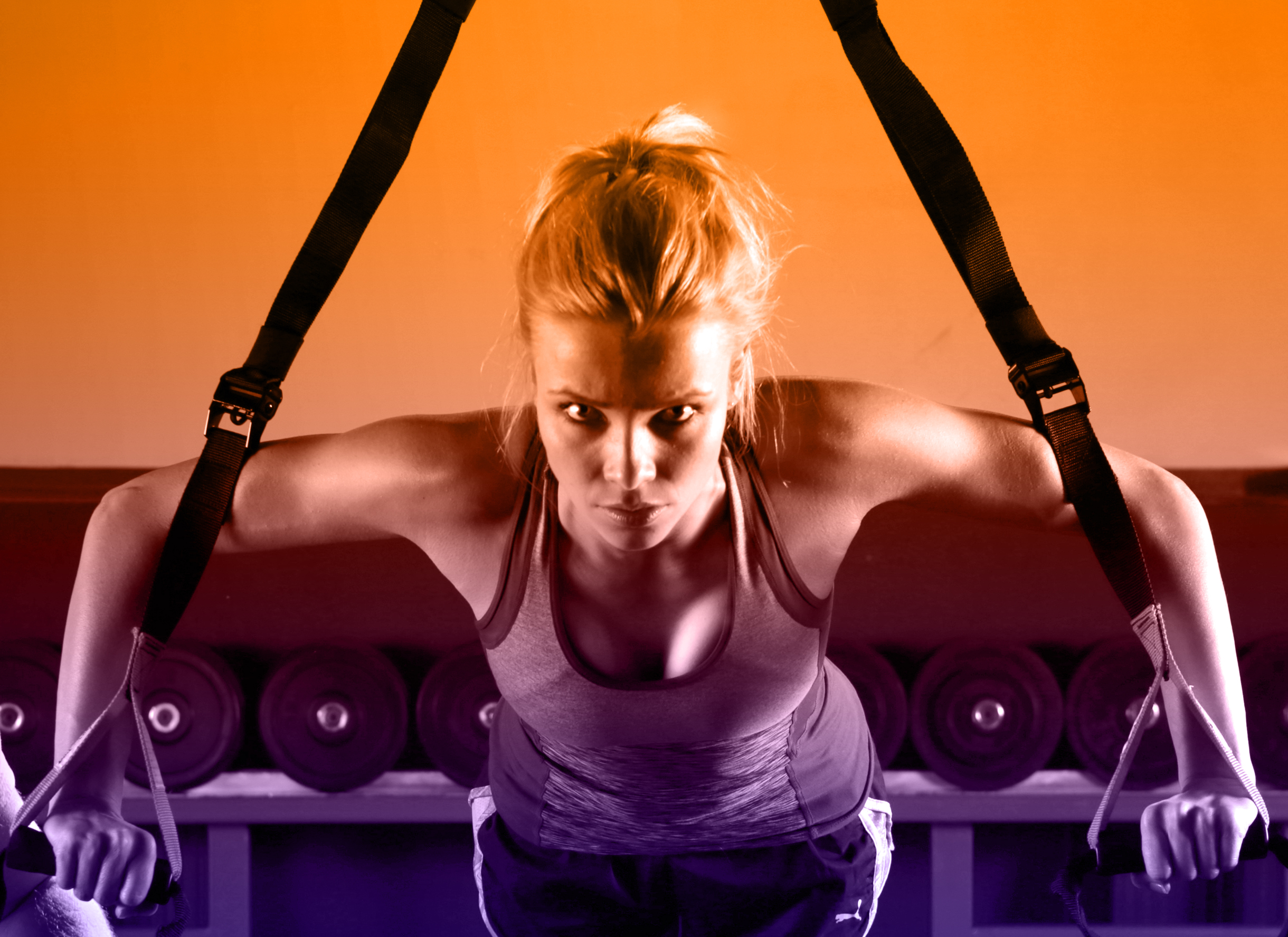 Young attractive woman training with htrx fitness straps in the gym photo