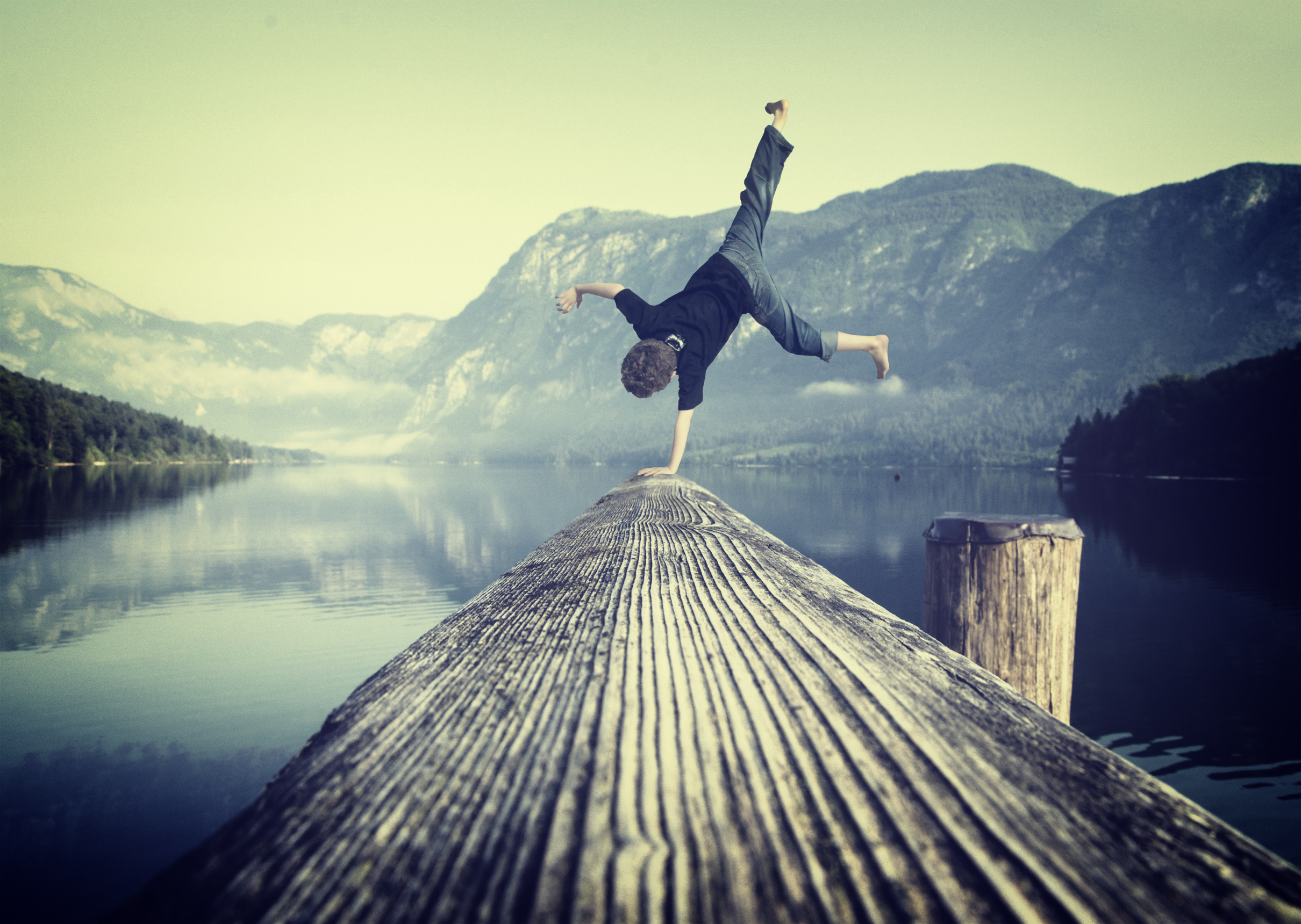 Young boy handstanding on jetty photo