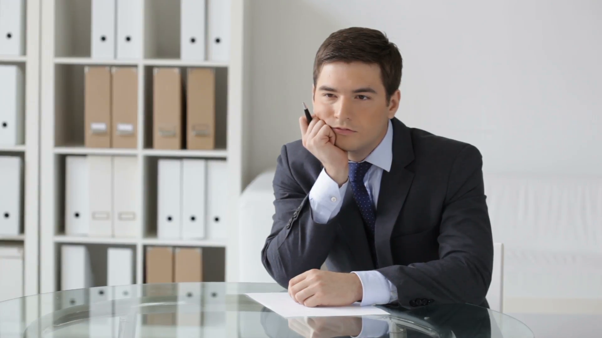 Young businessman thinking over the text of the business notice ...
