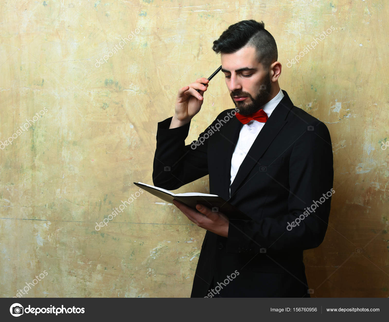 Young businessman with neat beard and haircut reading organizer ...