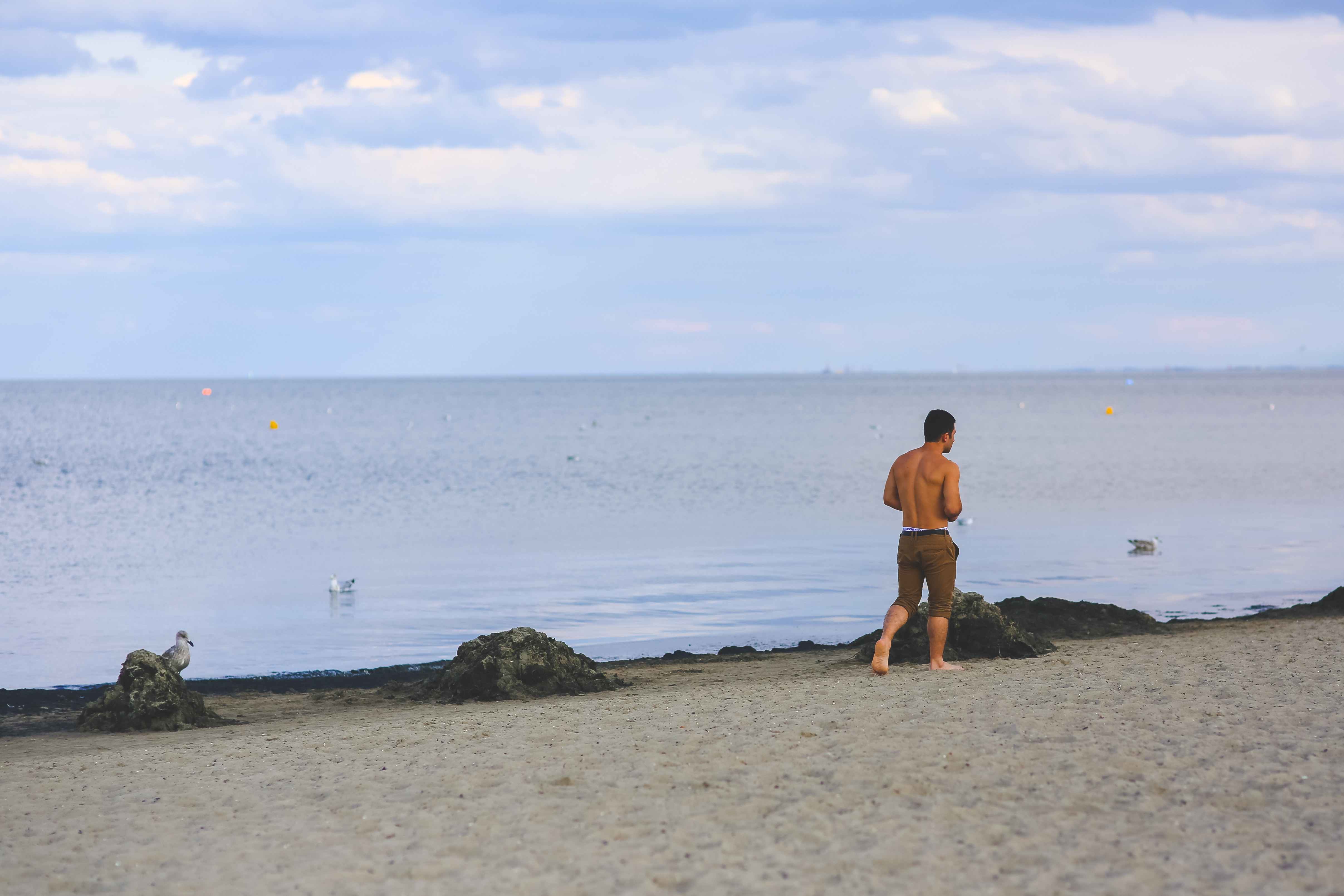 Young man walking on sand beach photo