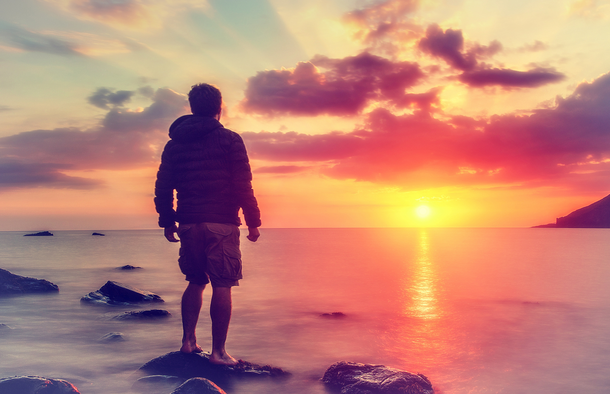 Young man watching the sunrise at rocky beach photo