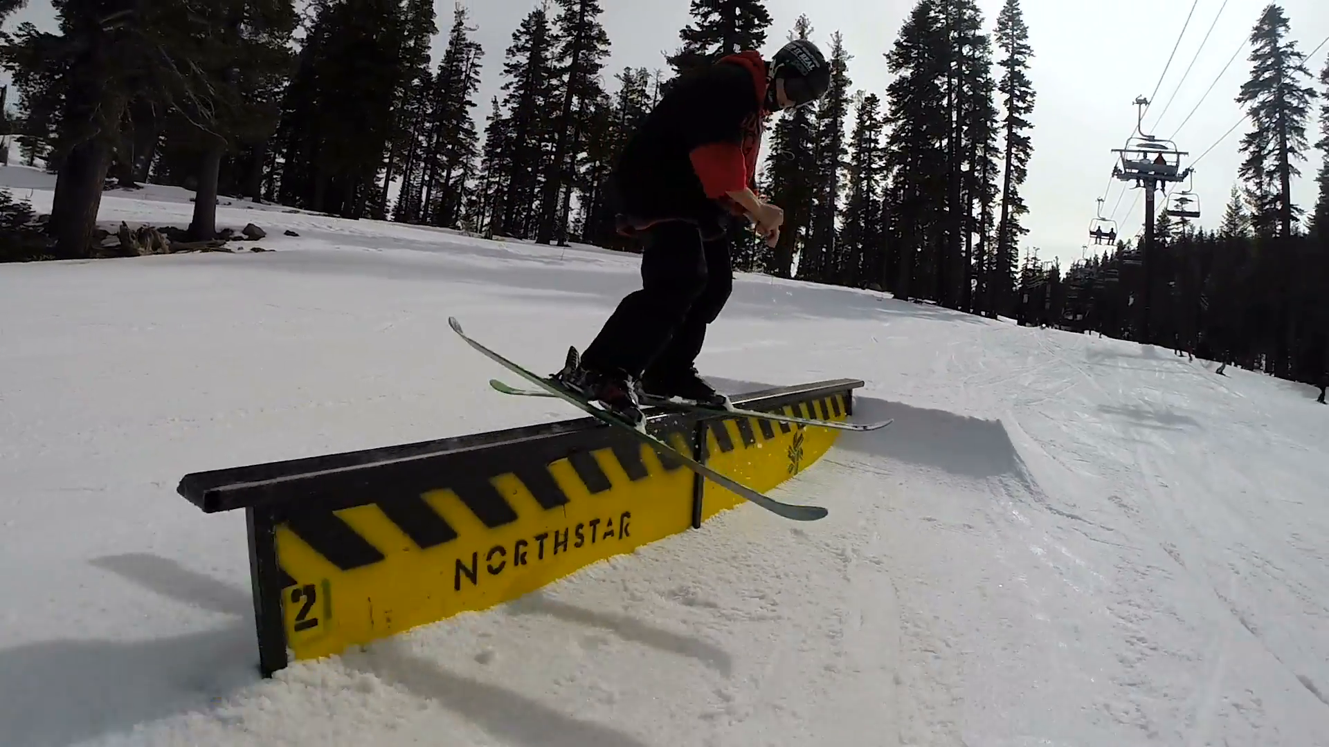 Young freeskier skiing a straight rail. Freestyle skier with twin ...