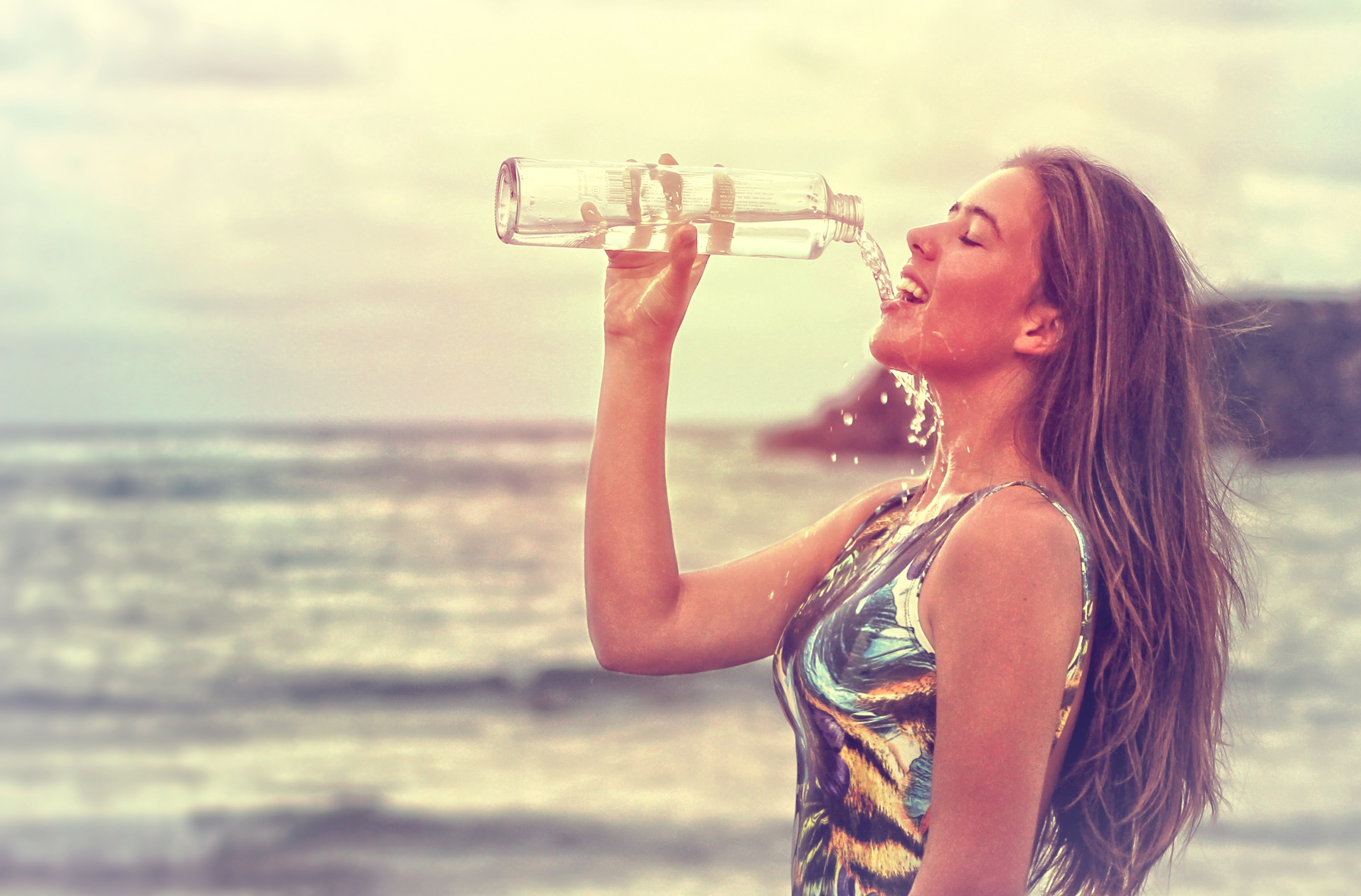 Young woman drinking sparkling water at the beach - health and fitness photo
