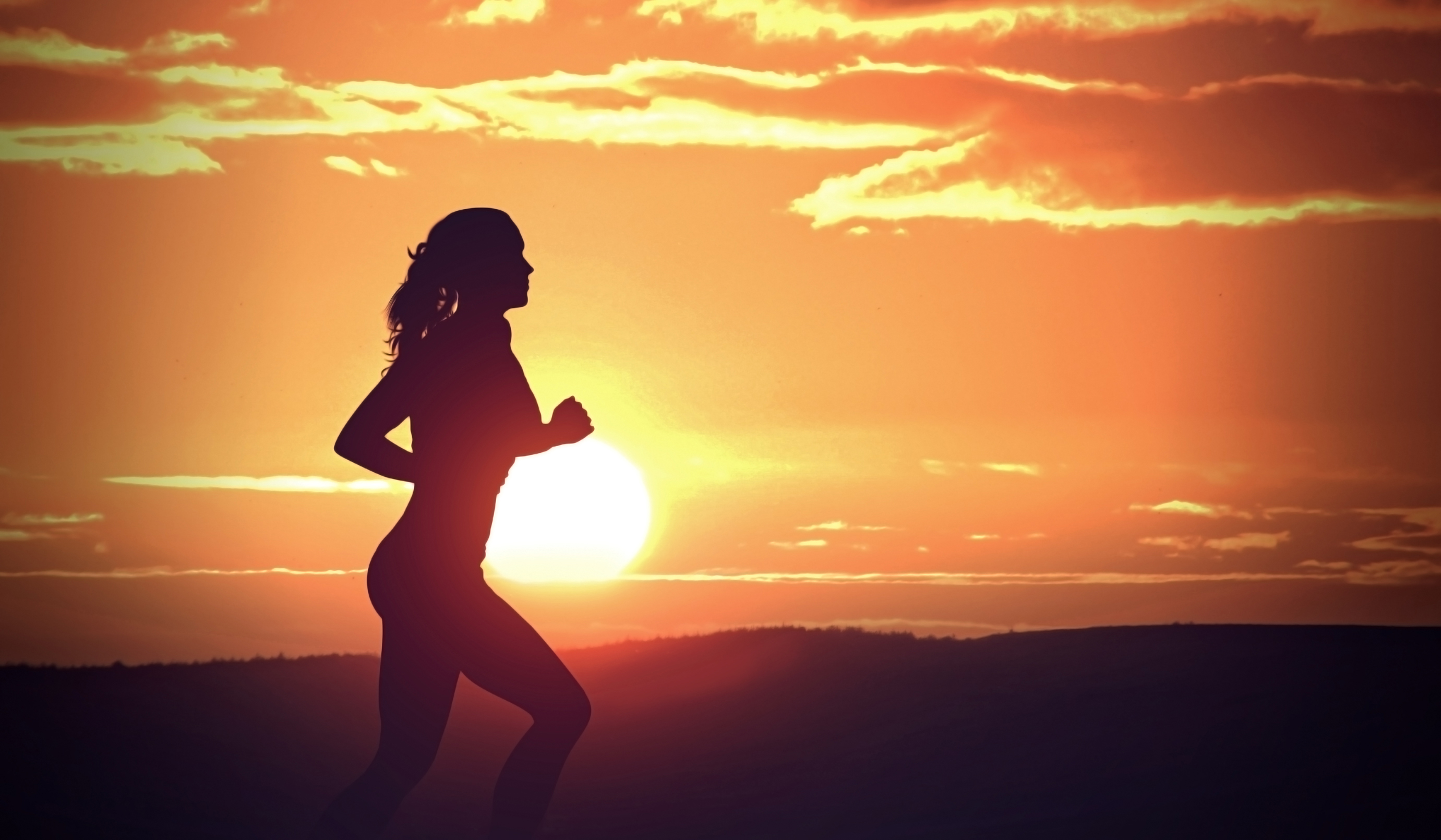 Young woman jogging at sunset photo