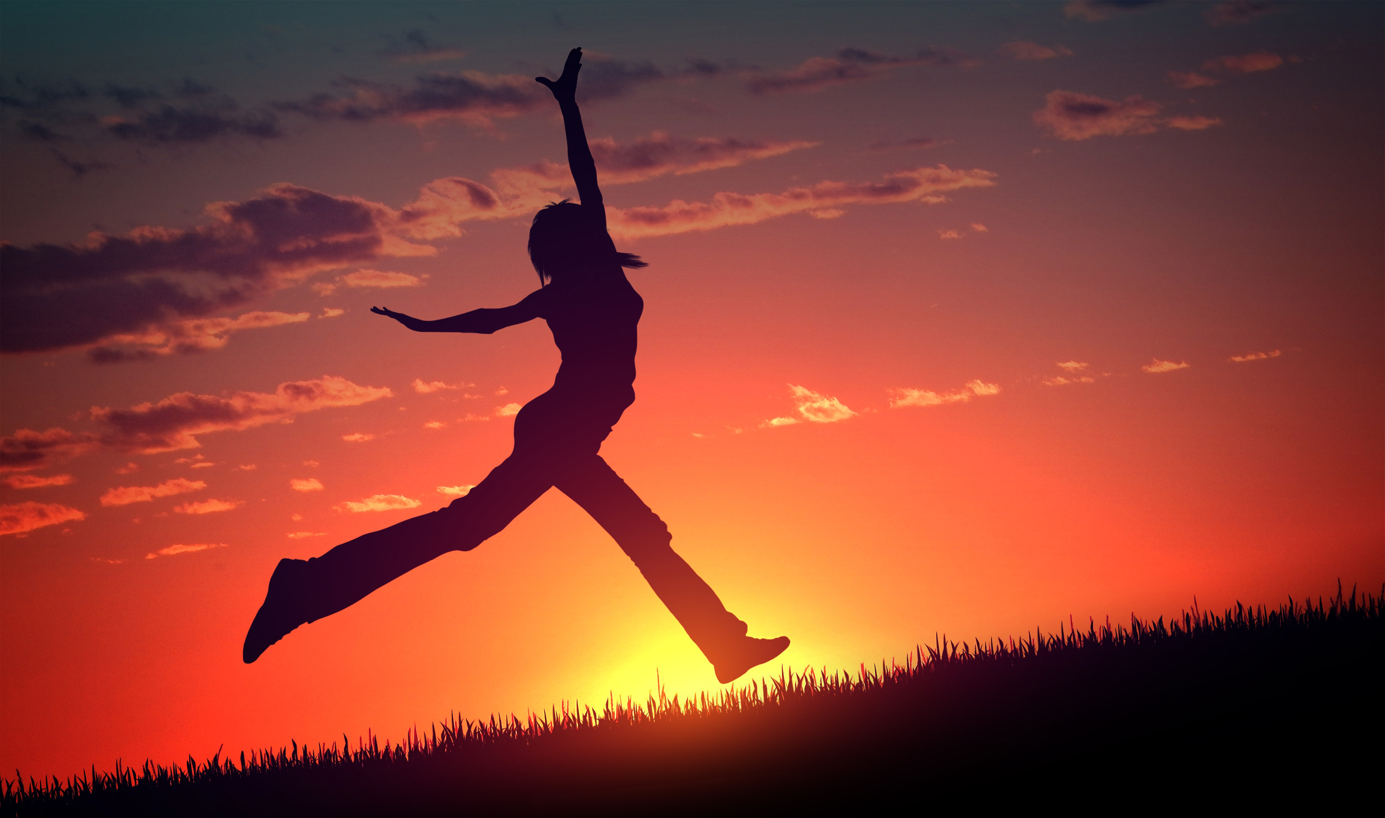 Young woman jumps at sunset photo