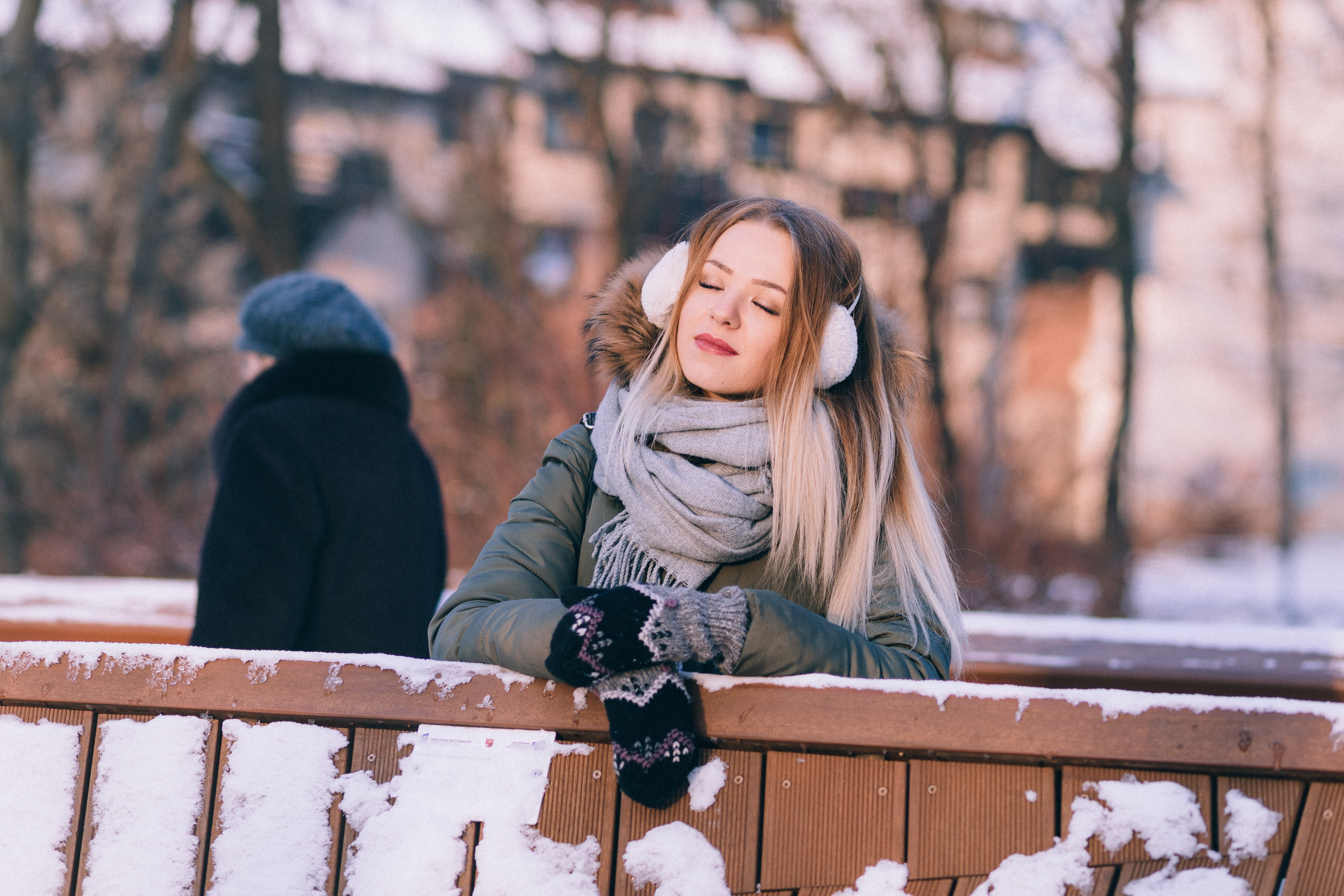 Young woman sitting on bench in winter photo