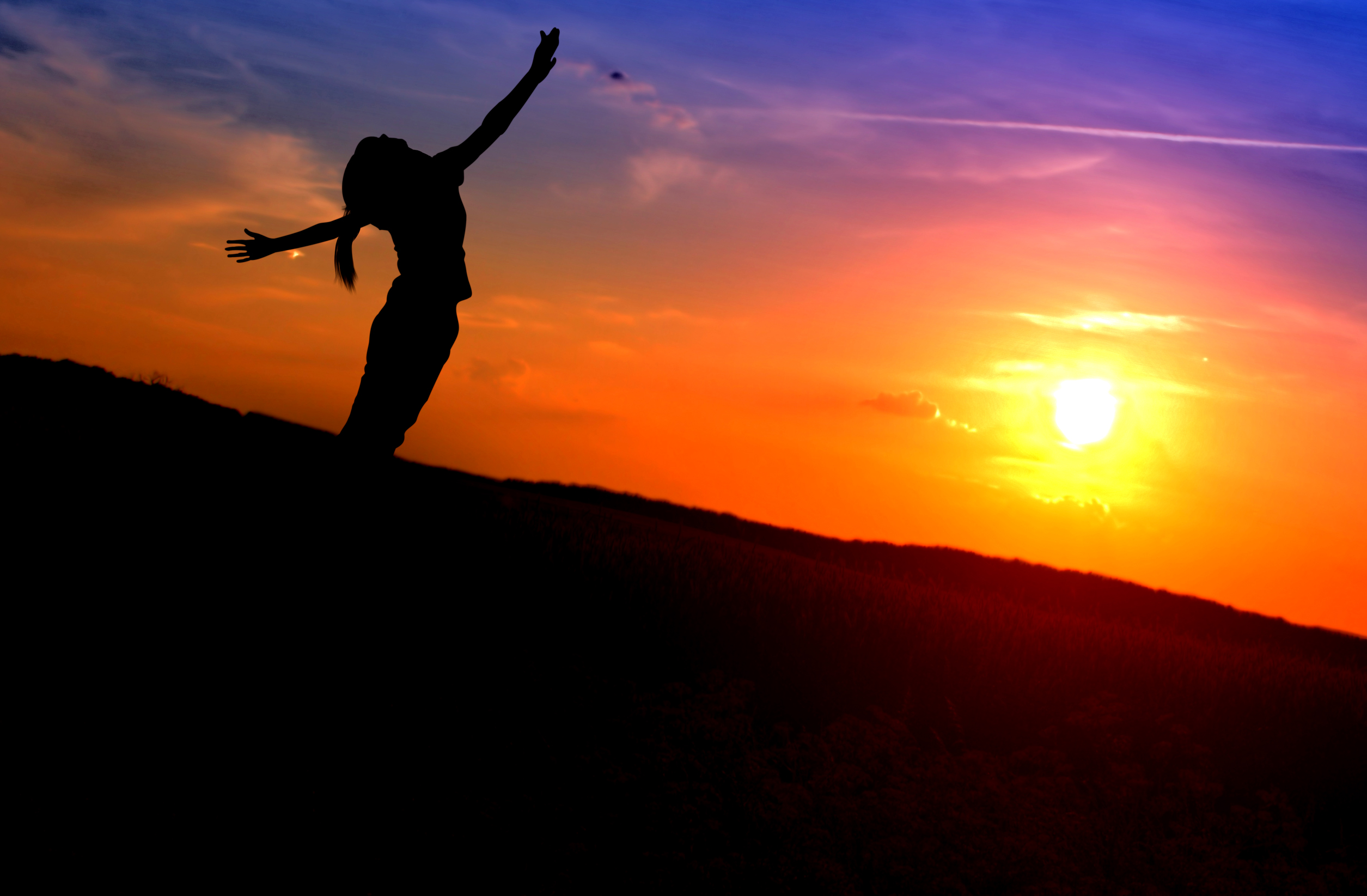 Young woman stretching her arms like wings at sunset photo