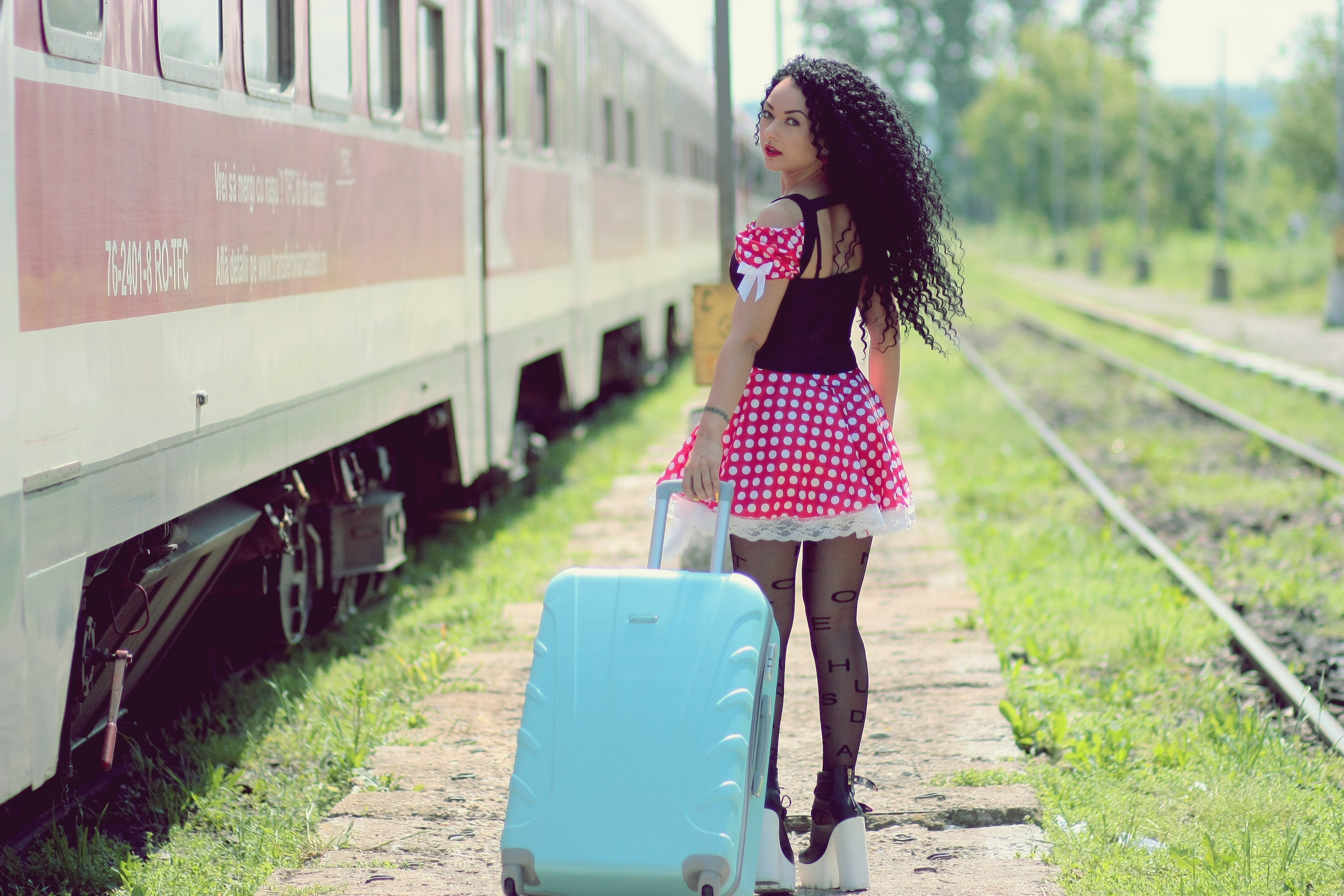 Young woman with luggage standing on train in city photo