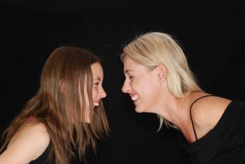 2 Women Smiling Near Black Textile
