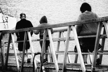 3 Person Walking on Bridge Black and White Photo