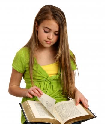 A beautiful young girl reading a book