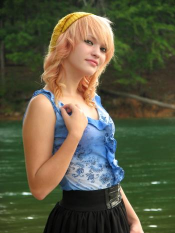 A beautiful young woman posing by a lake