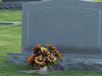 A blank tombstone with flowers