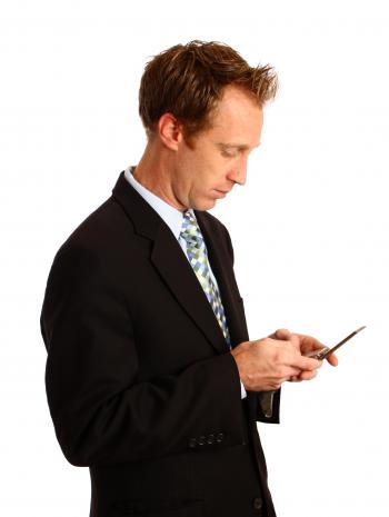A businessman texting on a cell phone