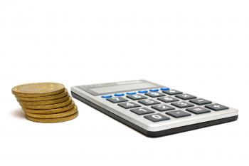 A calculator and a stack of gold coins